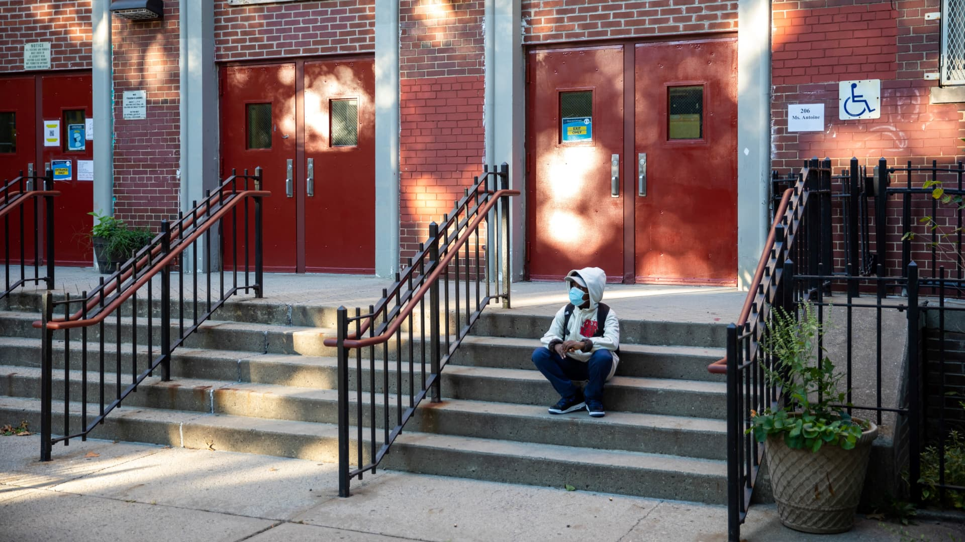 A student is seen on the steps of the closed public school PS 139 in the Ditmas Park neighborhood in Brooklyn of New York, the United States, Oct. 8, 2020.