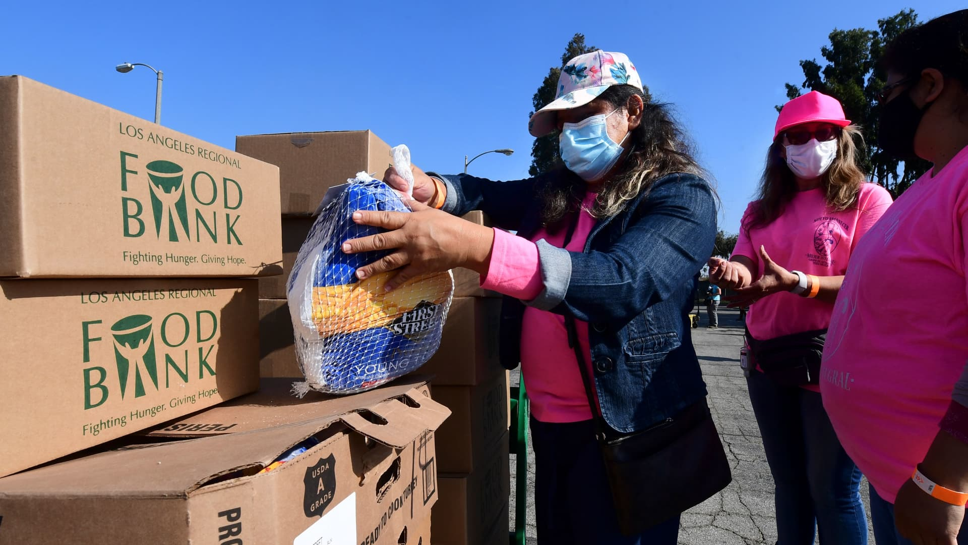 Volunteers from women's organization Nuevo Amanecer Mujer Integral help with the distribution of frozen turkeys and food boxes ahead of Thanksgiving to families affected by the Covid-19 pandemic on November 18, 2020 in Los Angeles, California.
