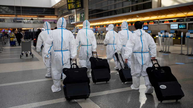 During the global coronavirus pandemica group of people wearing personal protective equipment walk in Tom Bradley international at LAX on Tuesday, Nov. 17, 2020 in Los Angeles, CA.