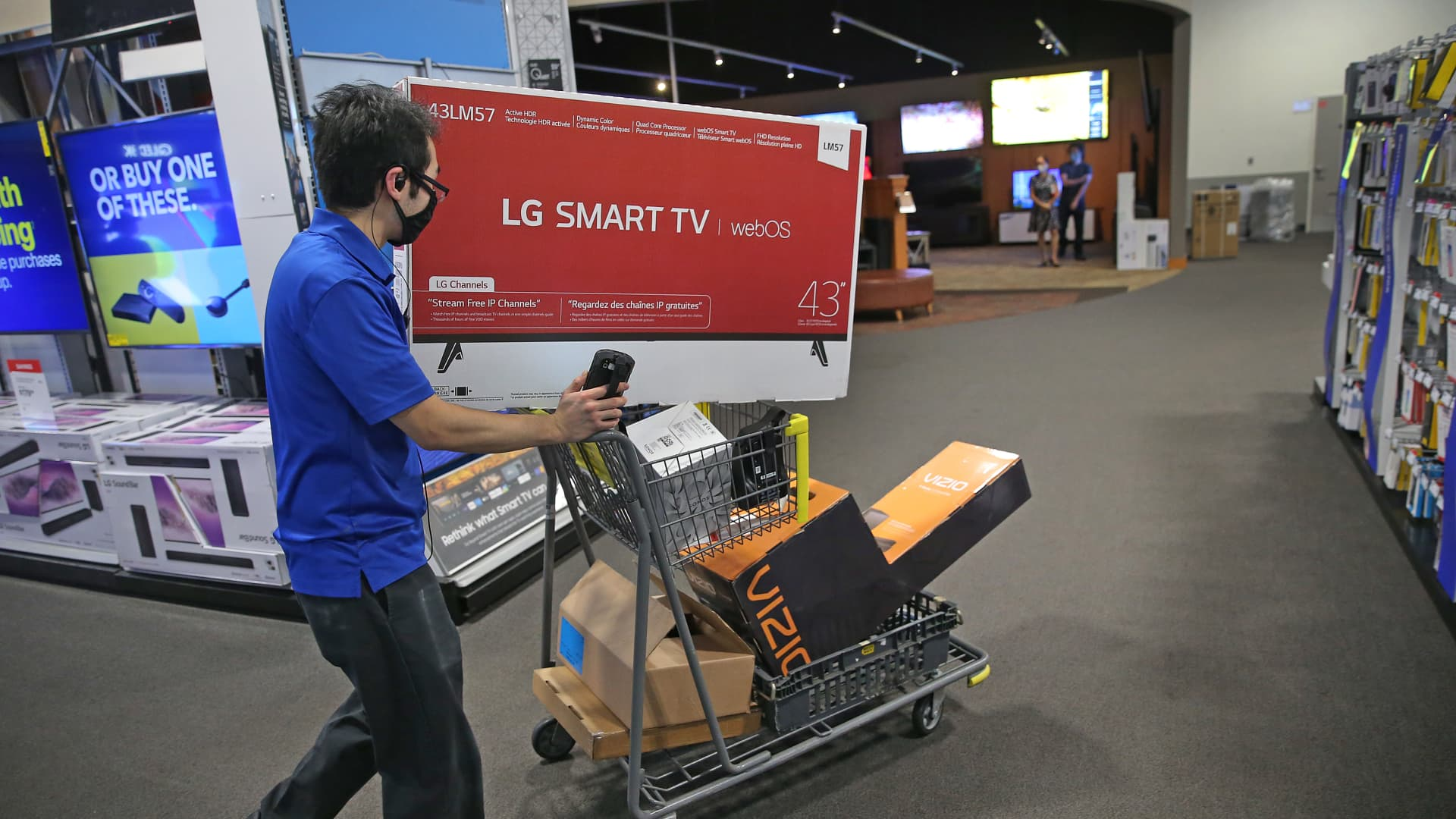 A Best Buy employee uses a cart to do shopping for an online customer at South Bay Center in Boston on Nov. 10, 2020. Retail trends are changing during the Covid-19 pandemic, and Best Buy has begun offering their holiday Black Friday sales and deals earlier in the month to thin out crowds.