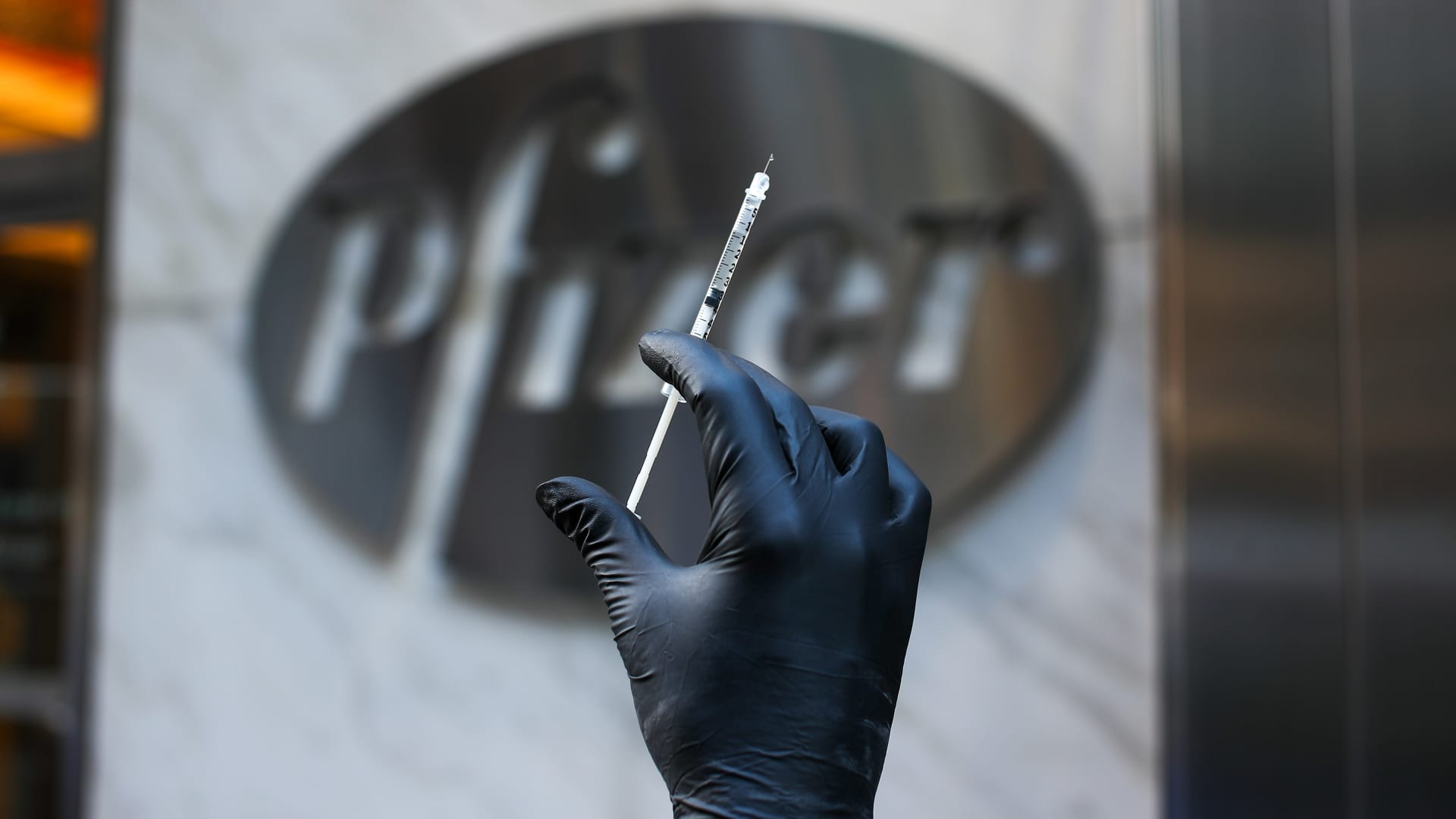 A syringe is seen by the logo of Pfizer's headquarter in Manhattan, New York City, United States on November 19, 2020.