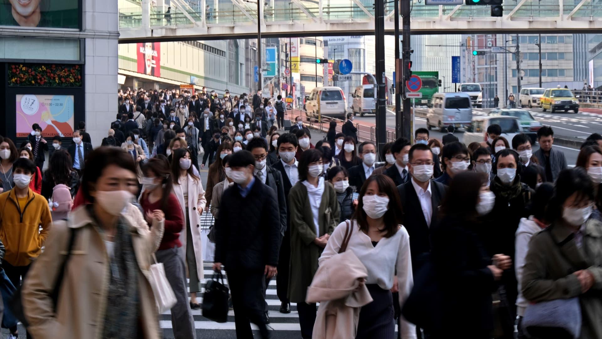 Commuters wearing masks walk near Shinjuku Station in Tokyo on November 19, 2020.