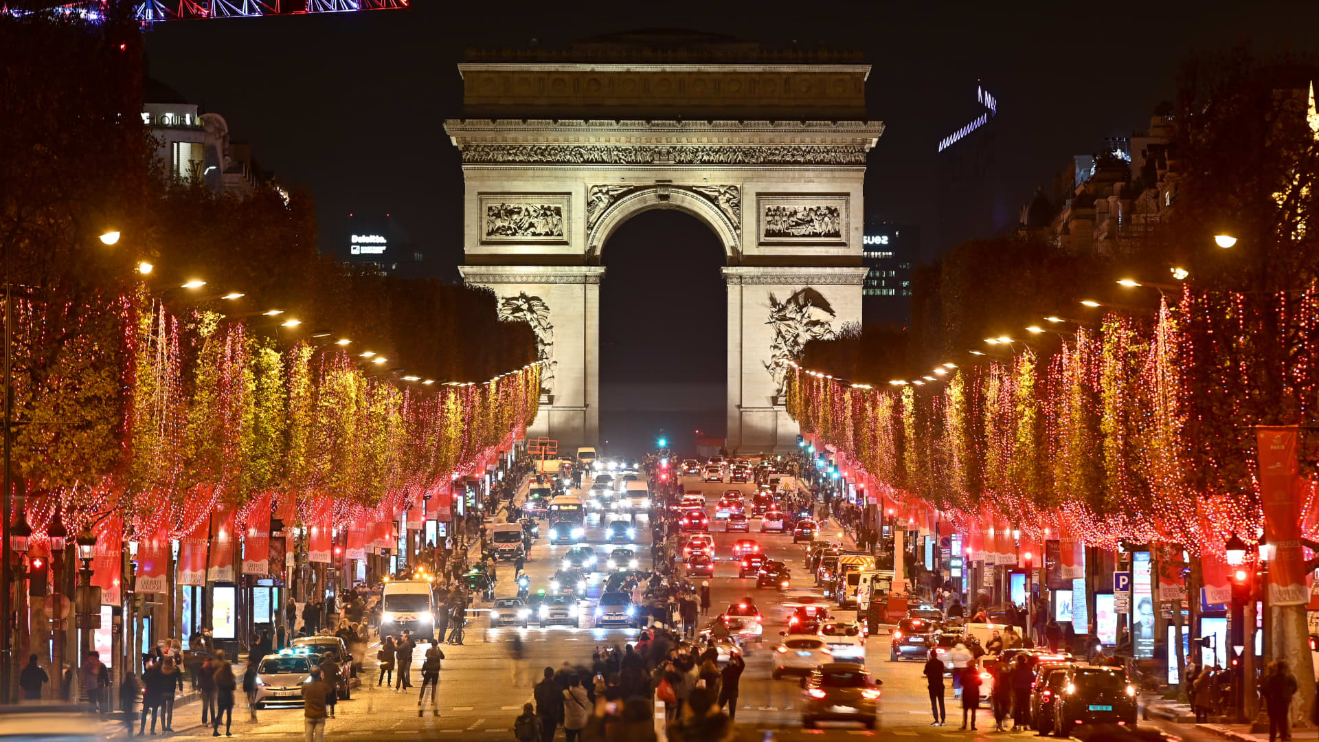 Red Christmas lights decorate the trees to illuminate the Champs-Elysees avenue with the Arc de Triomphe in the background for Christmas celebrations on November 22, 2020 in Paris, France.