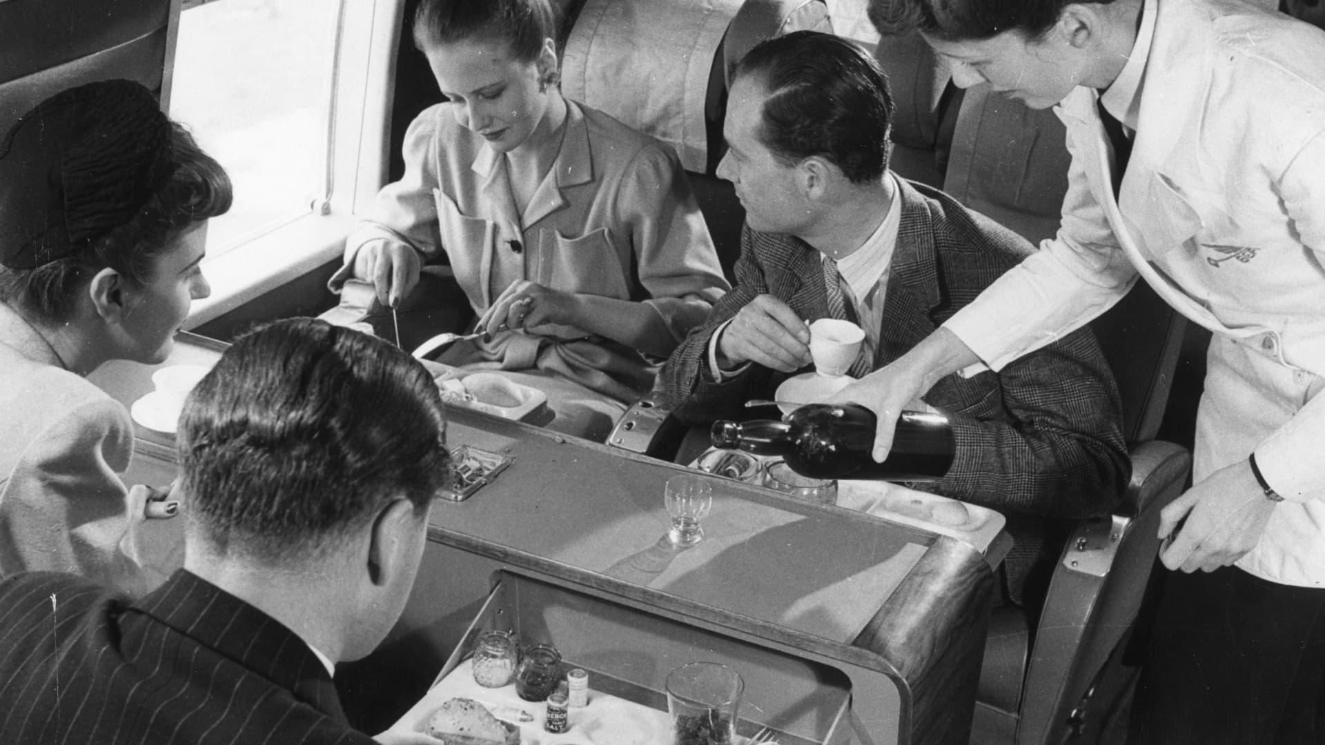 Passengers eat aboard a BEA Vickers Viking plane, circa 1958.