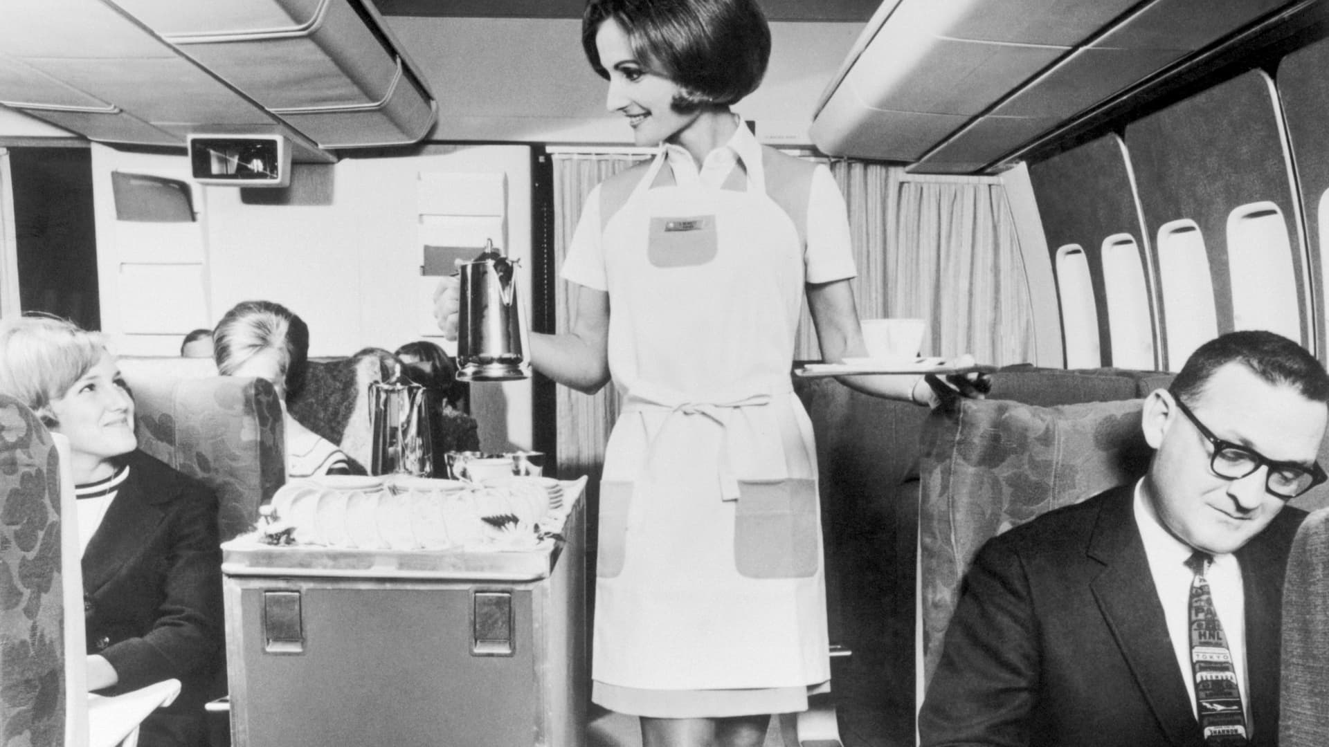 A flight attendant serves drinks in the economy section of a Pan Am 747.