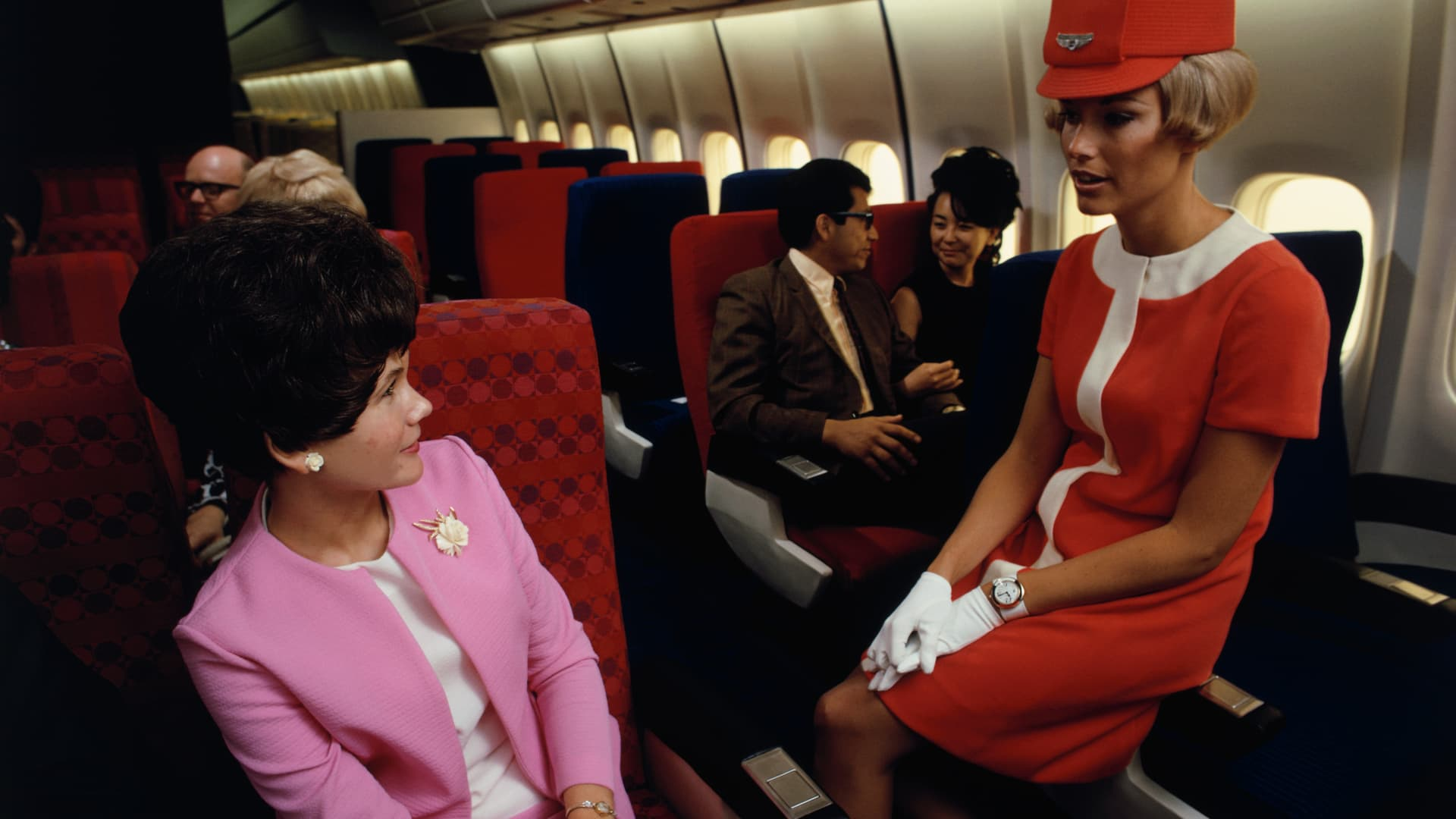 A United Airlines flight attendant talks with a passenger in a simulated passenger compartment of a Douglas DC-10.