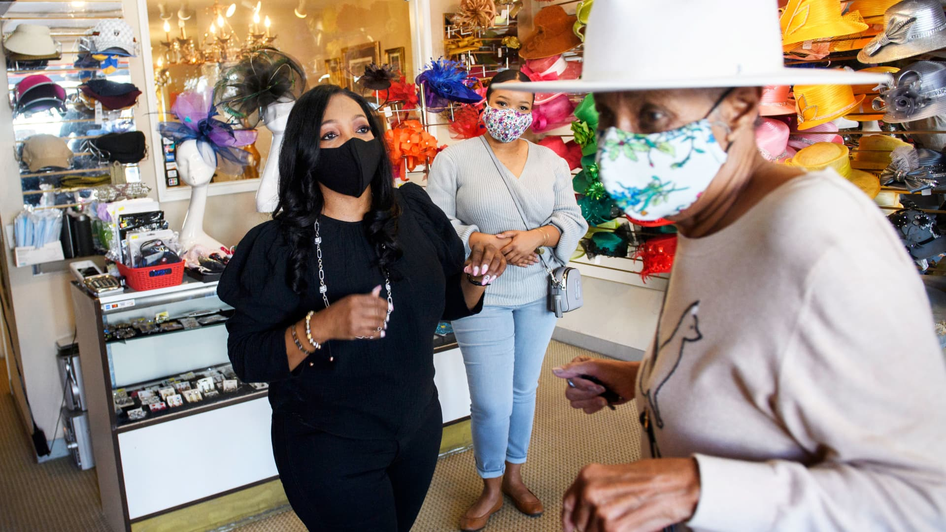 Customer Tamara Jenkins tries on a hat with Meeka Robinson Davis, owner of One-Of-A-Kind Hats, as Davis' daughter Chrstiana Davis looks on, at the store in the Windsor Hills neighborhood of Los Angeles, California, November 24, 2020.