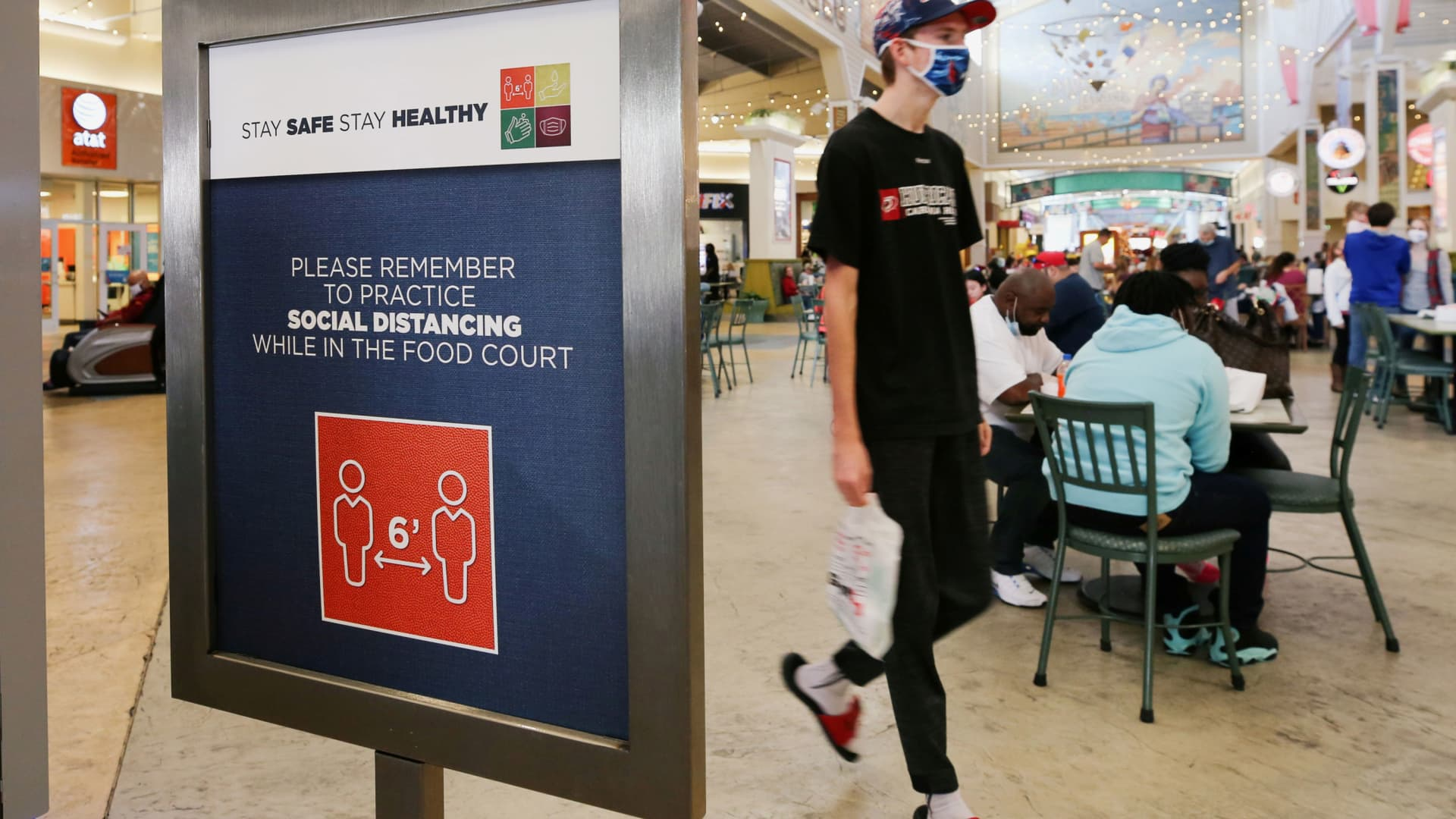 A shopper wearing a protective mask passes a social distancing sign at Coastal Grand Mall on Black Friday, in Myrtle Beach, South Carolina, November 27, 2020.