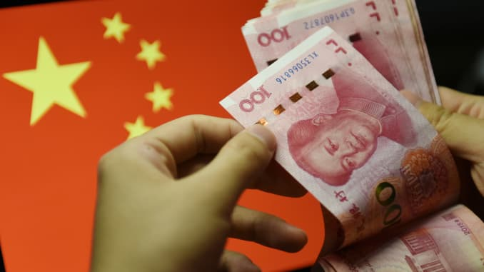 A man counts 100 RMB notes with the Chinese flag in the background.