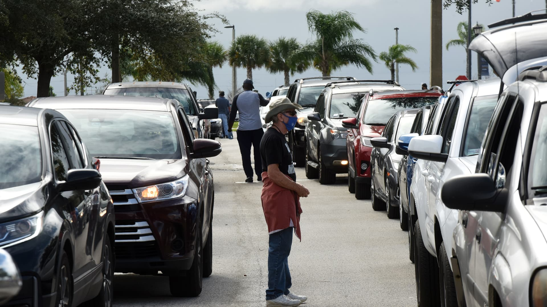 Volunteers direct traffic as residents line up in their cars at a food distribution site at Lake-Sumter State College sponsored by the Second Harvest Food Bank of Central Florida and local churches.