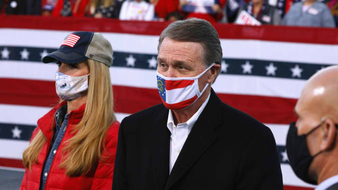 Republican Senators David Perdue and Kelly Loeffler look on ahead of U.S. President Donald Trump hosting a campaign event with Perdue and Loeffler at Valdosta Regional Airport in Valdosta, Georgia, U.S., December 5, 2020.