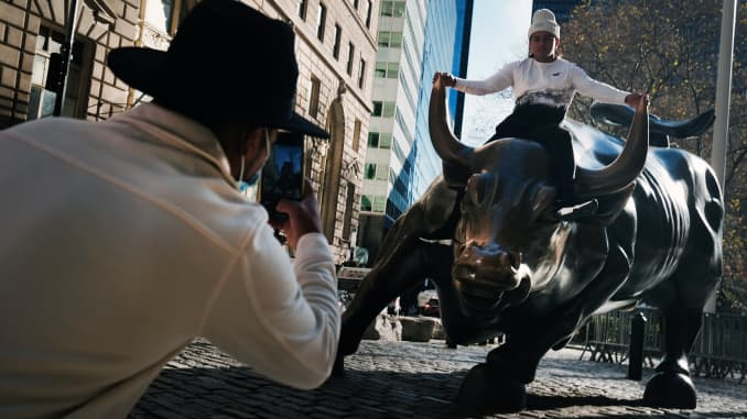 A man sits on the Wall street bull near the New York Stock Exchange (NYSE) on Nov. 24, 2020 in New York City.
