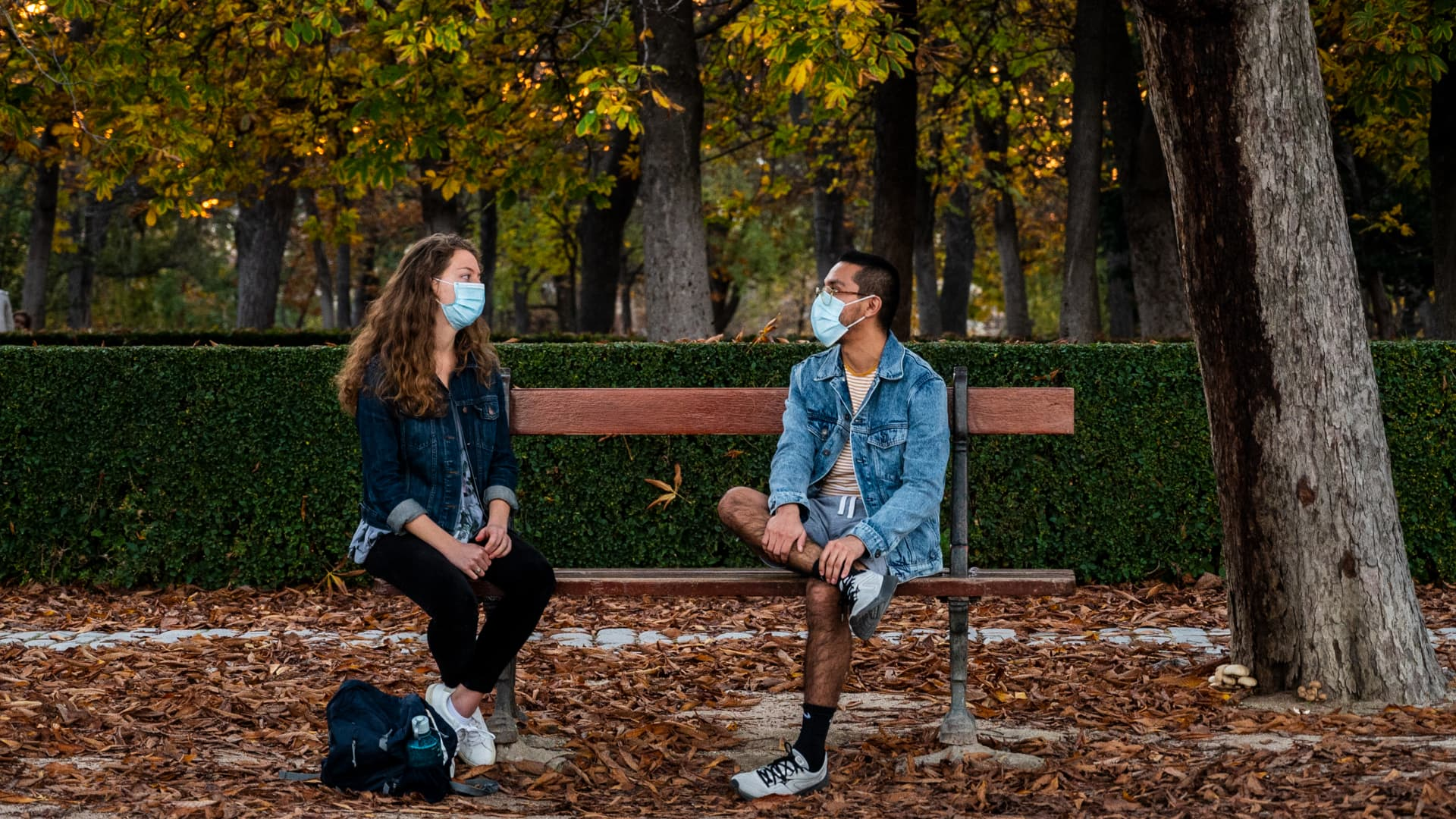 A couple wearing face masks to protect against the spread of coronavirus (COVID-19) sitting on a bench maintaining social distance in the Retiro Park in Madrid, Spain.