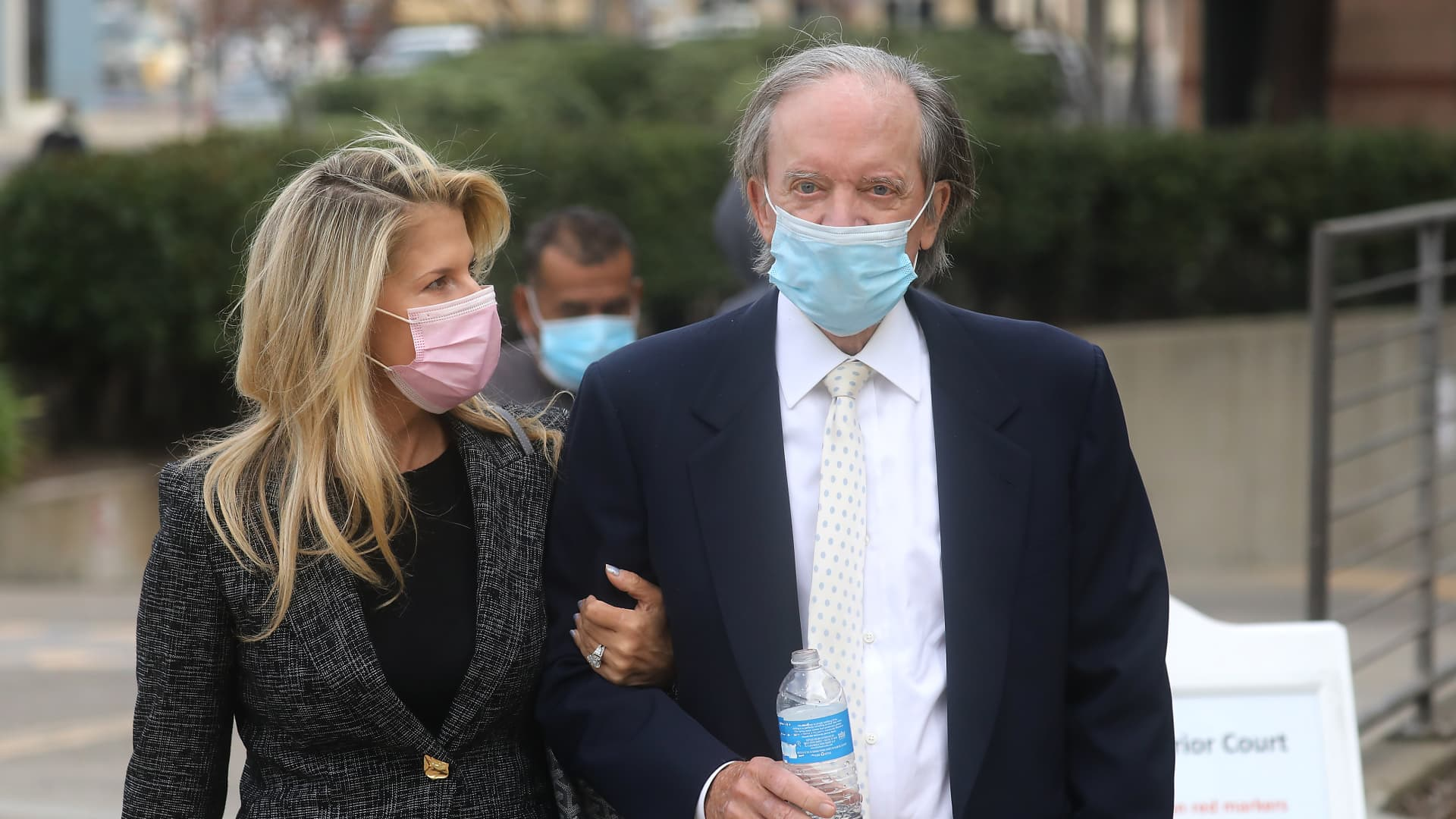 Bill Gross, co-founder of Pacific Investment Management Co. (PIMCO), and his girlfriend Amy Schwartz wear protective masks while arriving at state court in Santa Ana, California, U.S., on Monday, Dec. 7, 2020.