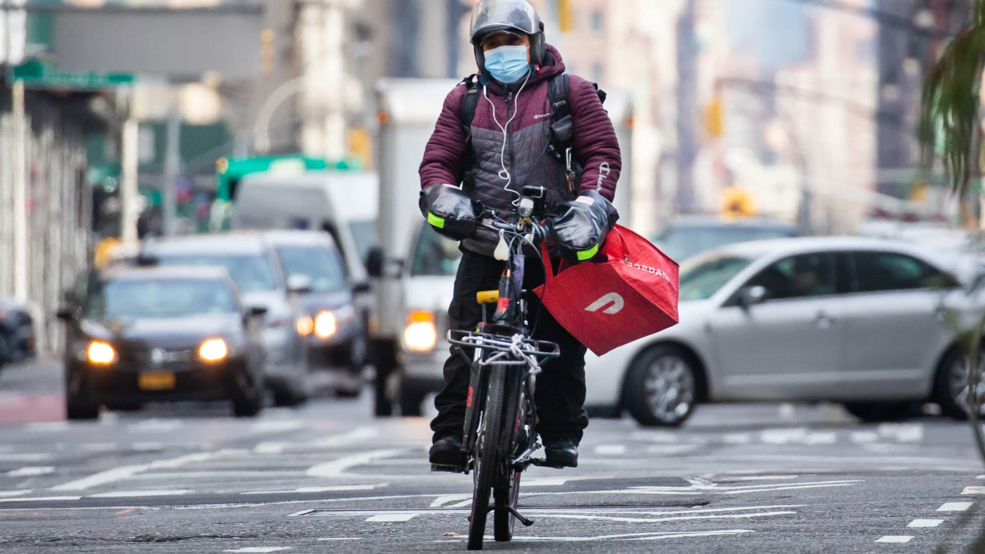 A bike messenger carries a DoorDash bag during a delivery in New York, Wednesday, Dec. 9, 2020.