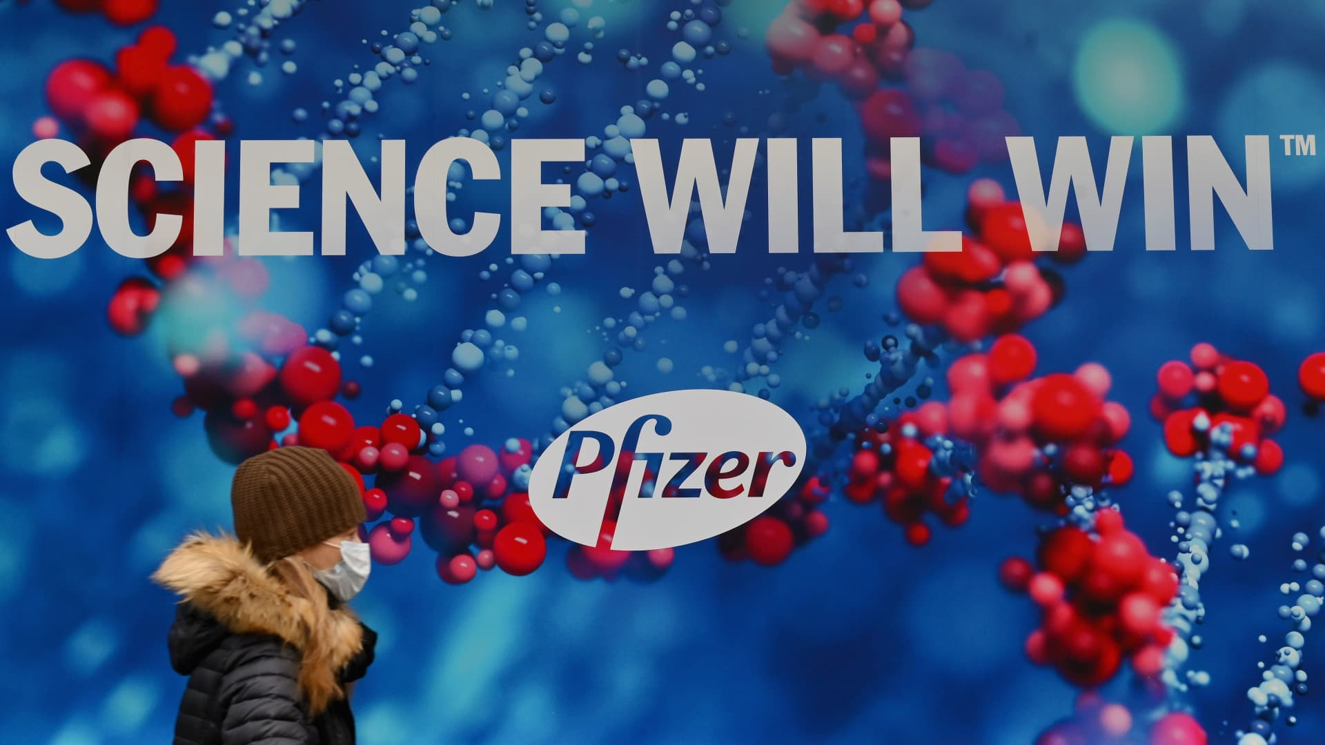 A person wearing a protective face mask walks past the Pfizer Inc. headquarters on December 9, 2020 in New York City.