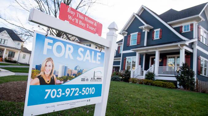 Bảng hiệu rao bán bất động sản của một ngôi nhà được nhìn thấy trước một ngôi nhà ở Arlington, Virginia, ngày 19 tháng 11 năm 2020.