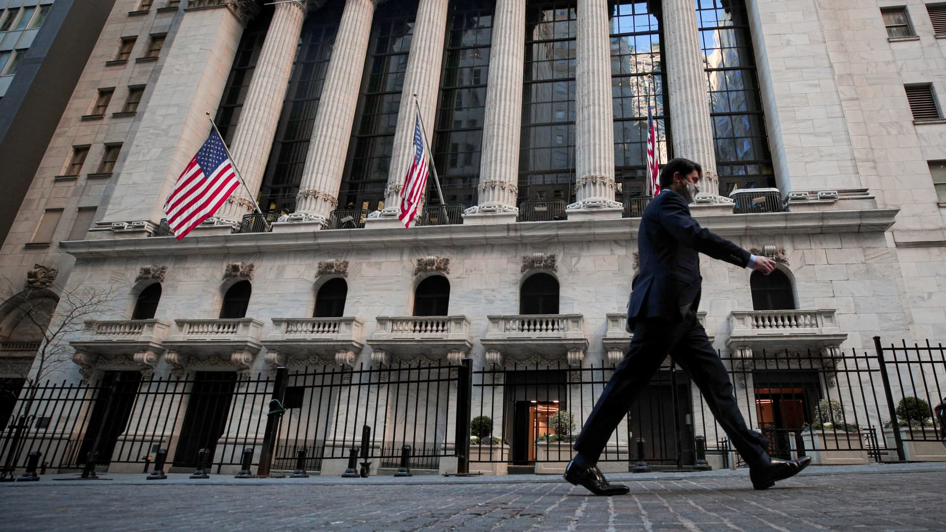 A man walks outside the New York Stock Exchange (NYSE) in New York, November 24, 2020.