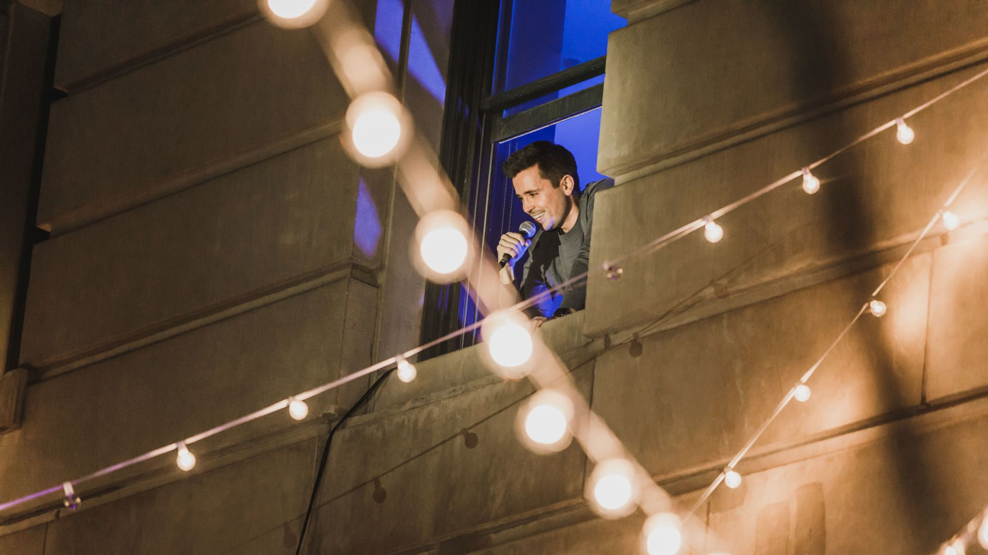 Broadway actor Matt Doyle sings out the window of Room 201 at the Ace Hotel to diners down below.