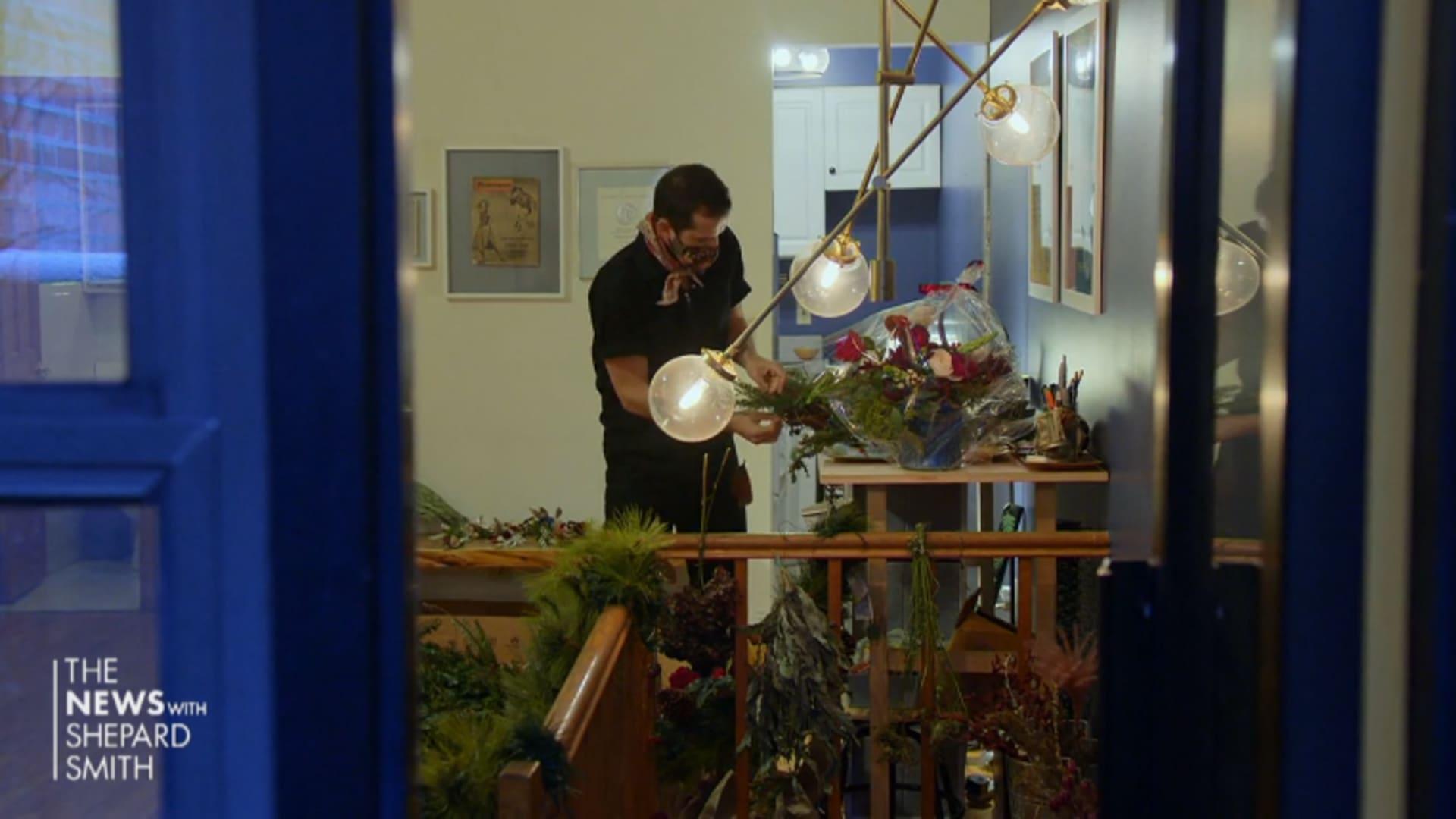 Actor Robbie Fairchild works on a flower arrangement inside his New York City apartment