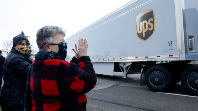Nancy Galloway (L) and Susan Deur cheer as trucks carrying the first shipment of the Covid-19 vaccine that is being escorted by the US Marshals Service, leave Pfizer's Global Supply facility in Kalamazoo, Michigan on December 13, 2020.