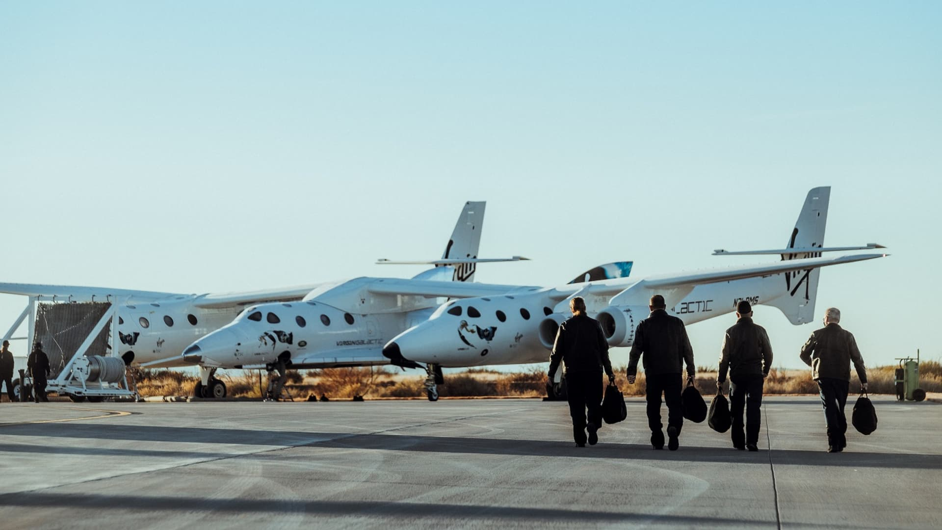 Virgin Galactic pilots walk to the company's SpaceShipTwo Unity spacecraft, attached to the jet carrier aircraft Eve.