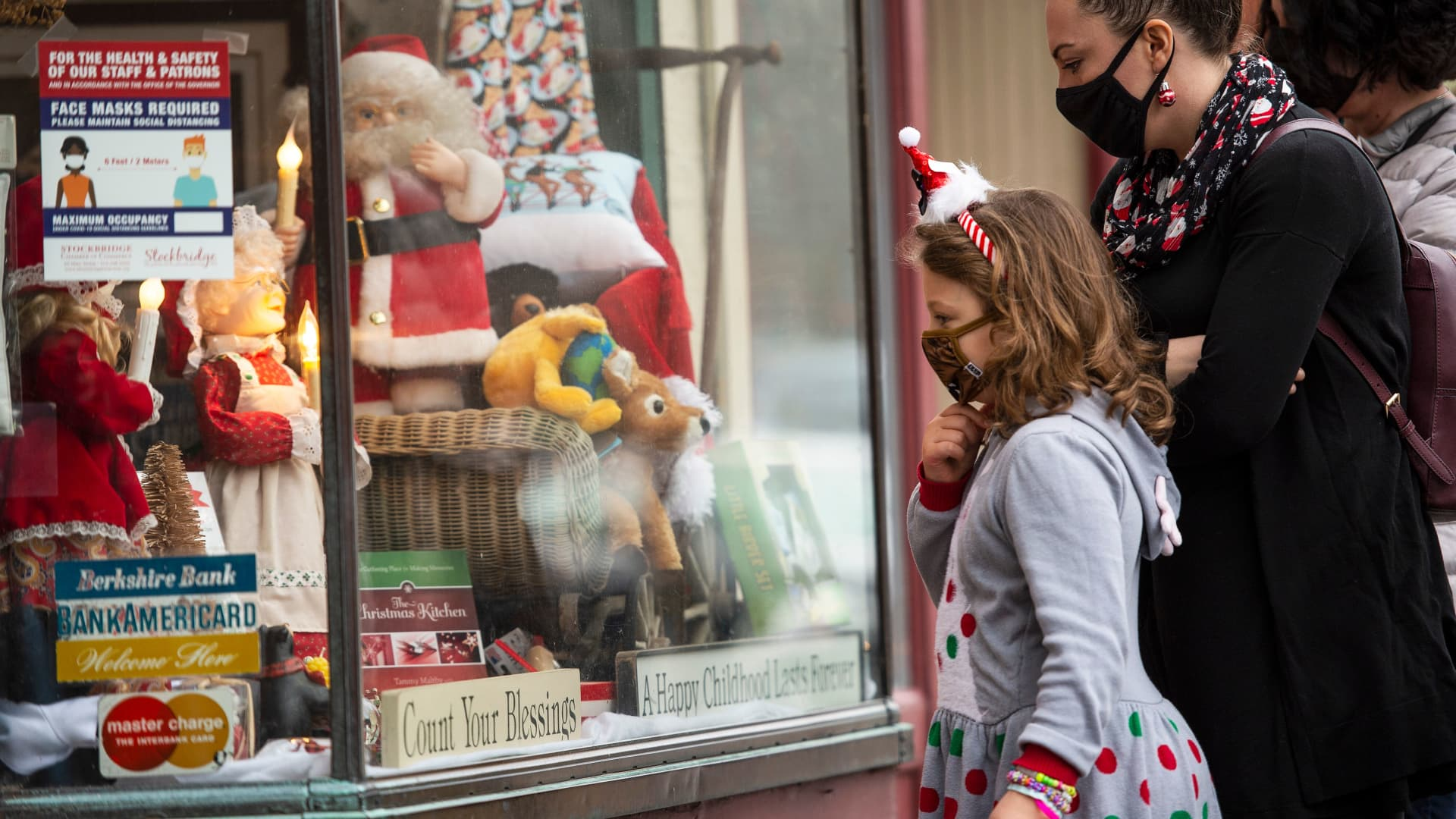 People look at the holiday decorations in the window displays at the Country store on Main Street in Stockbridge, Massachusetts on December 13, 2020.