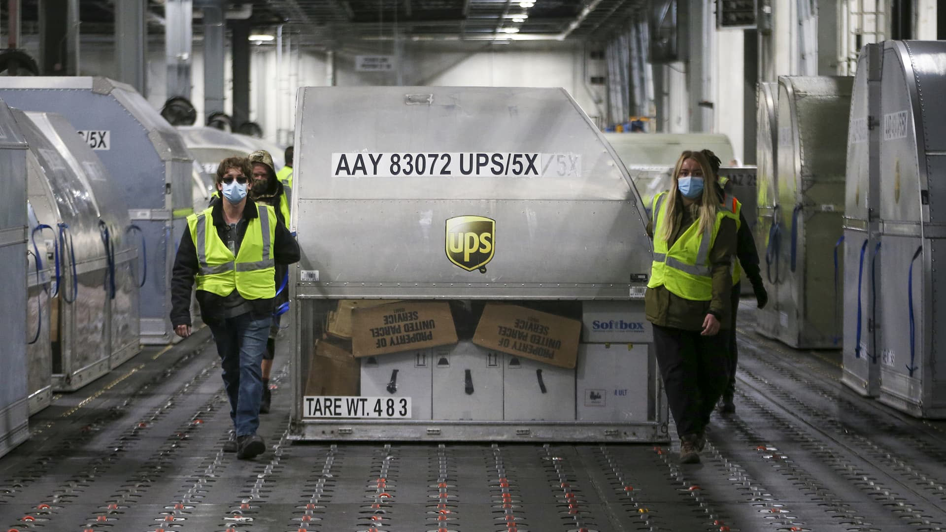 UPS employees move one of two shipping containers containing the first shipments of the Pfizer and BioNTech Covid vaccine inside a sorting facility at UPS Worldport on December 13, 2020 in Louisville, Kentucky.