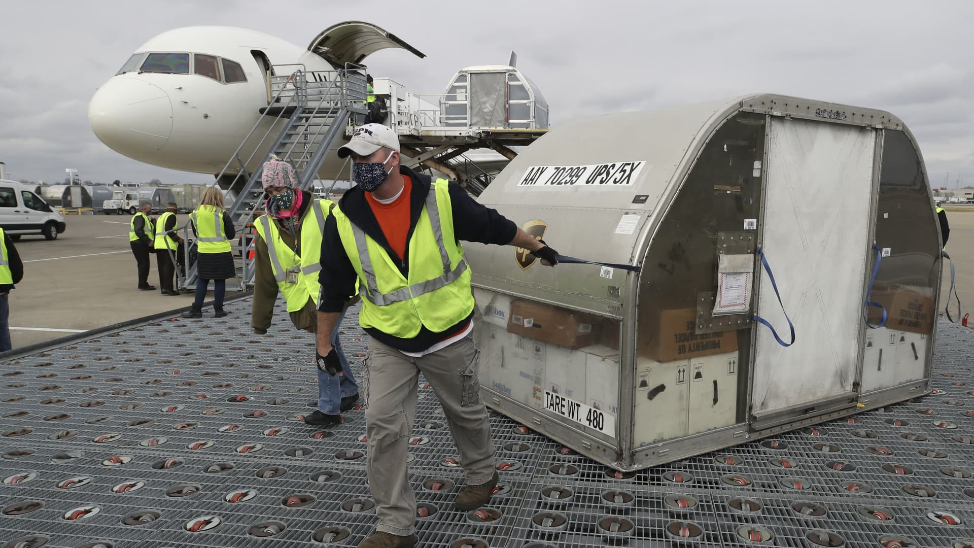 UPS employees move one of two shipping containers containing the first shipments of the Pfizer and BioNTech COVID-19 vaccine on a ramp at UPS Worldport in Louisville, Kentucky, on Sunday, December 13, 2020.
