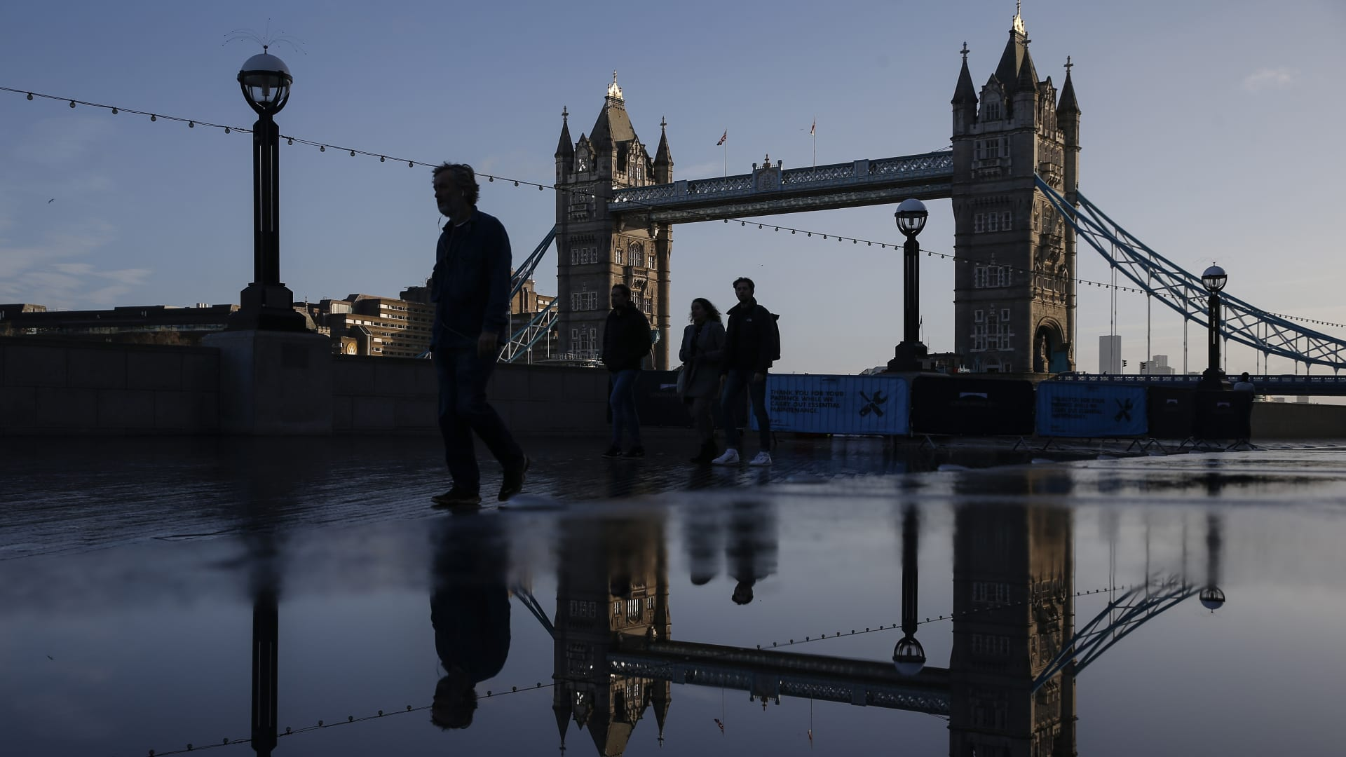 Commuters walk along the Thames Path in view of Tower Bridge in London, U.K., on Monday, Dec. 14, 2020.