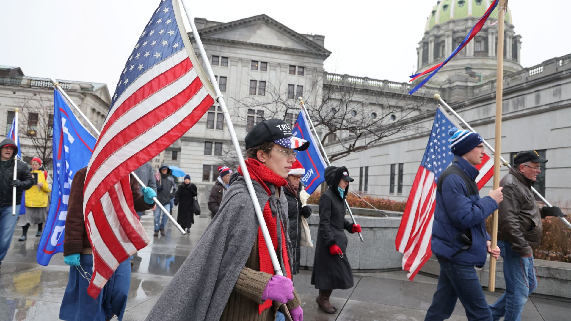 A small band of Trump supporters march with flags as electors gathered to cast their votes for the U.S. presidential election at the State Capitol complex in Harrisburg, Pennsylvania, U.S. December 14, 2020.