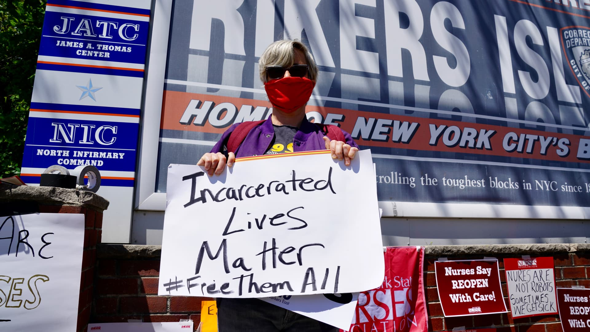 A nurse holds a sign during a nurses protest at Rikers Island Prison over conditions and coronavirus threat on May 7, 2020 in New York City.