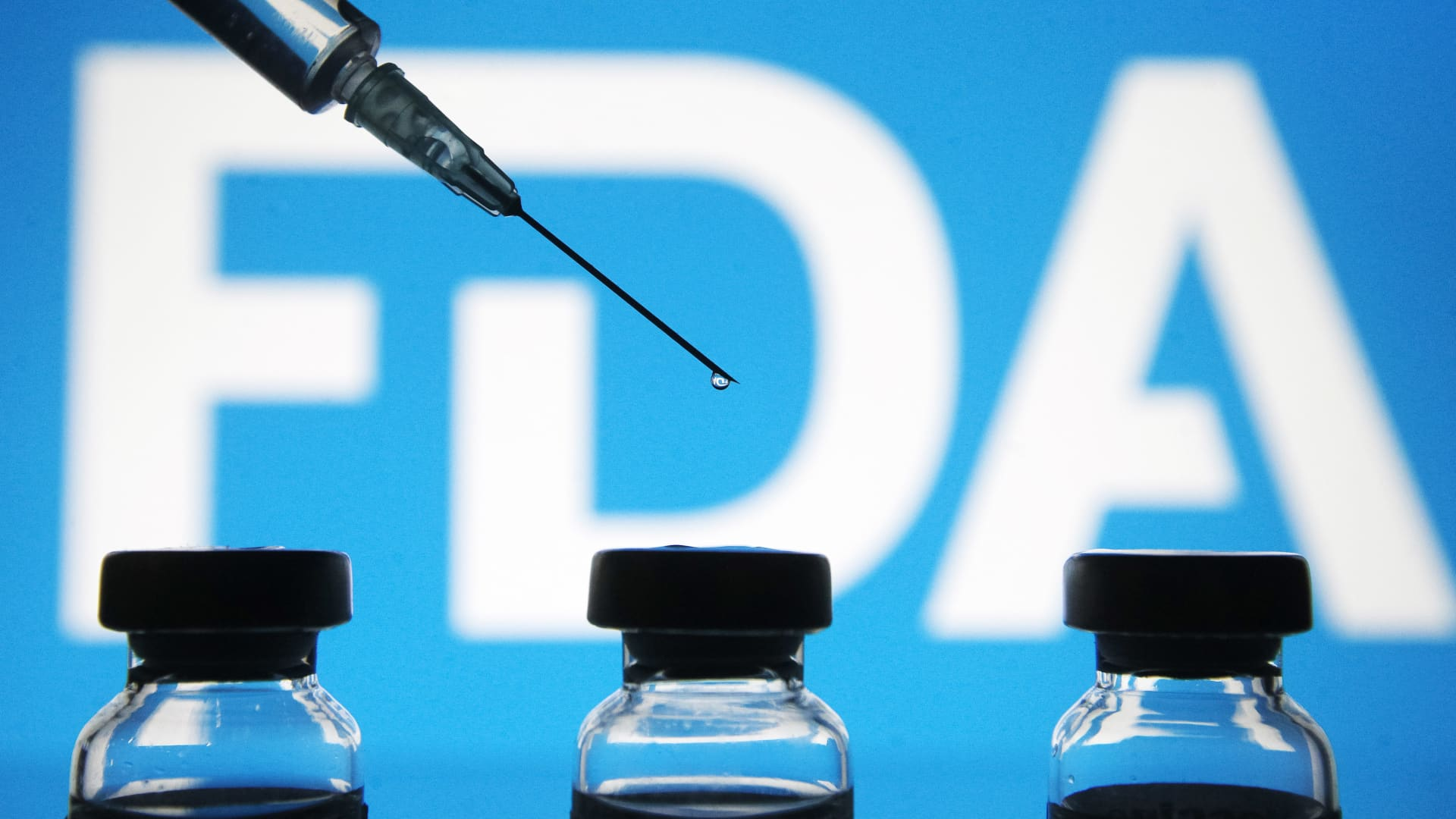 Vials and a medical syringe seen displayed in front of the Food and Drug Administration (FDA) of the United States logo. FDA finds the COVID-19 vaccine.