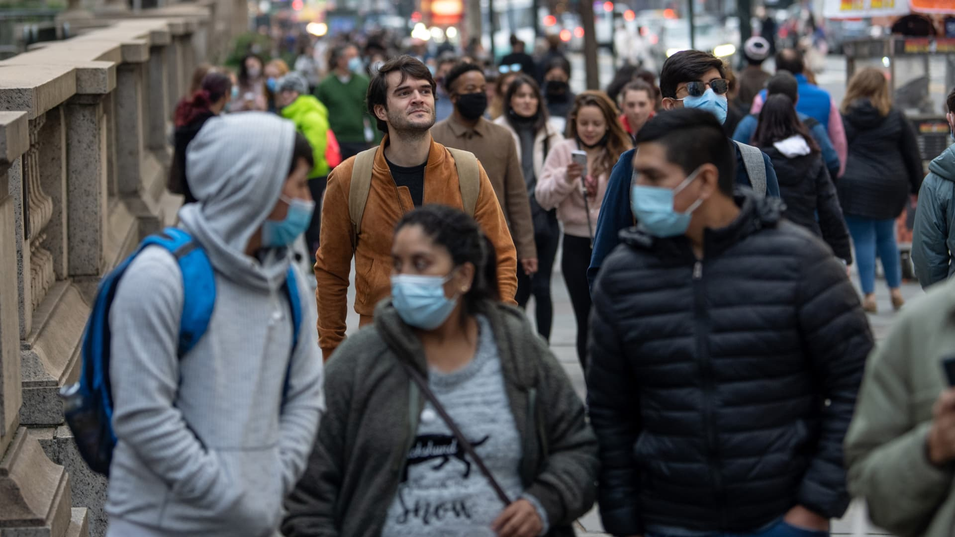 A man without a mask walks through a crowd of people on Dec. 13, 2020 in New York.