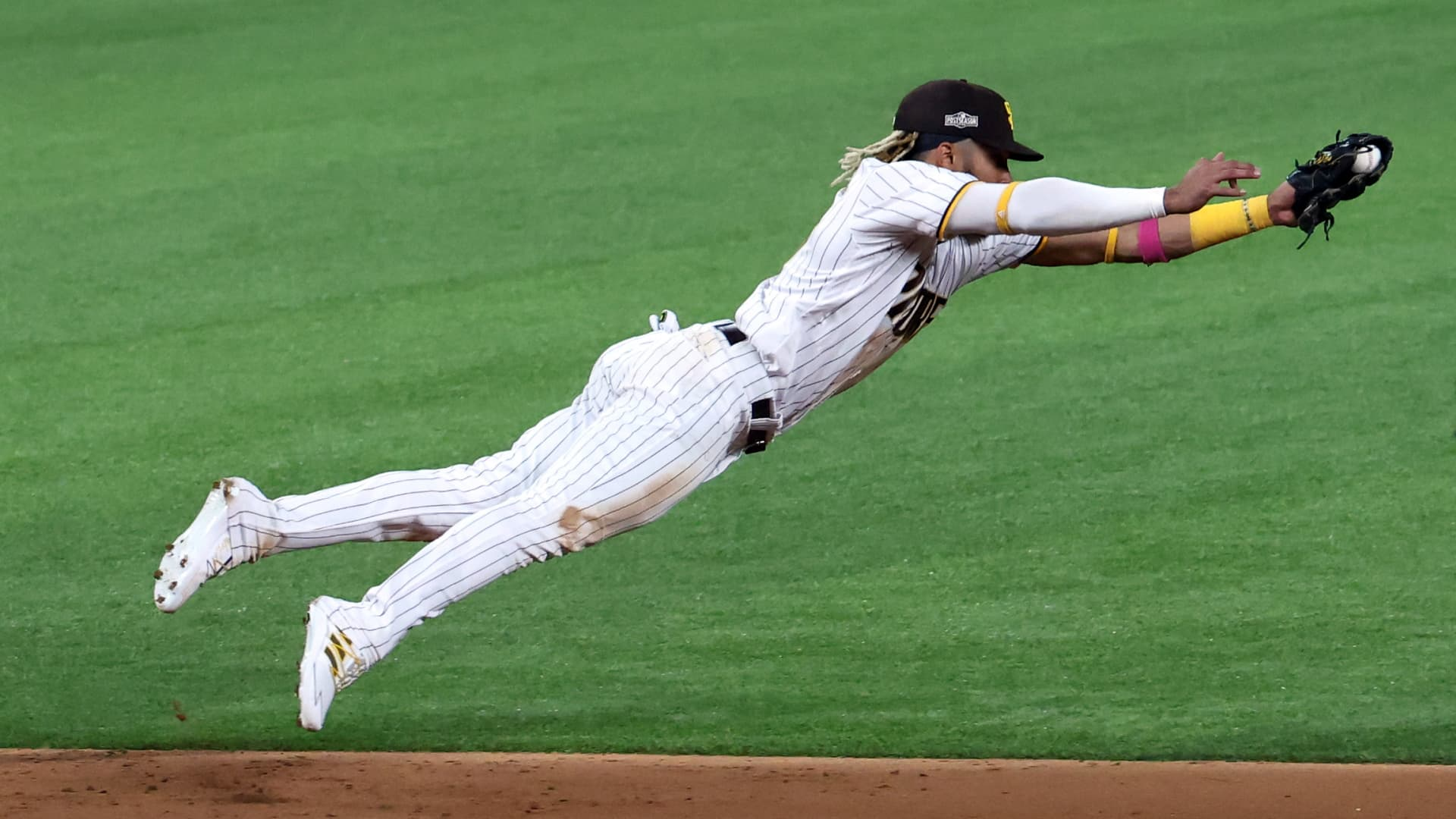 Fernando Tatis Jr. #23 of the San Diego Padres dives to cut off a ball hit by Corey Seager #5 of the Los Angeles Dodgers (not pictured) during the third inning in Game Three of the National League Division Series at Globe Life Field on October 08, 2020 in Arlington, Texas.