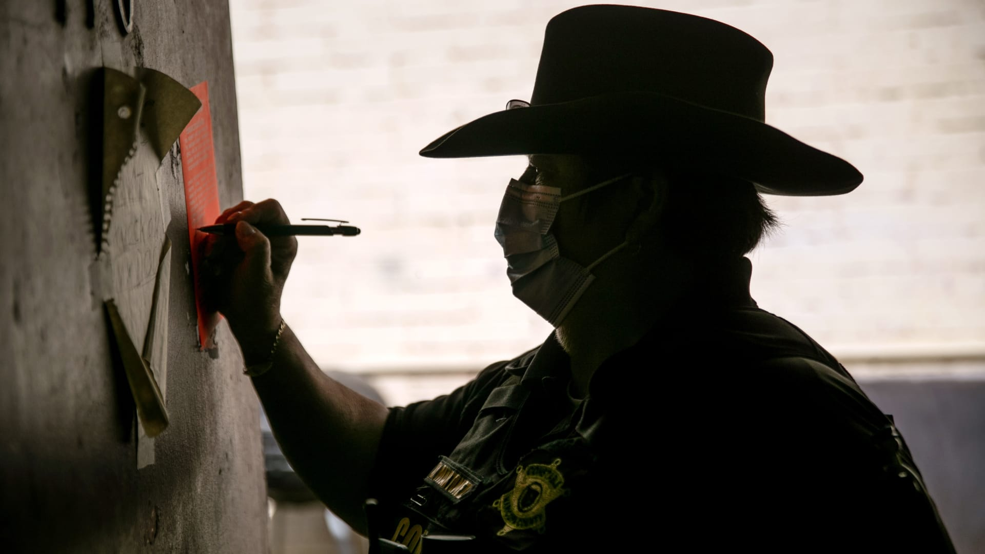 Maricopa County constable Darlene Martinez signs an eviction order on Oct. 7, 2020 in Phoenix, Arizona.