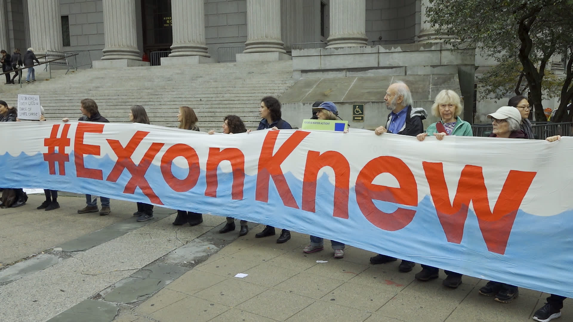 People protest against ExxonMobil before the start of its trial outside the New York State Supreme Court building on October 22, 2019