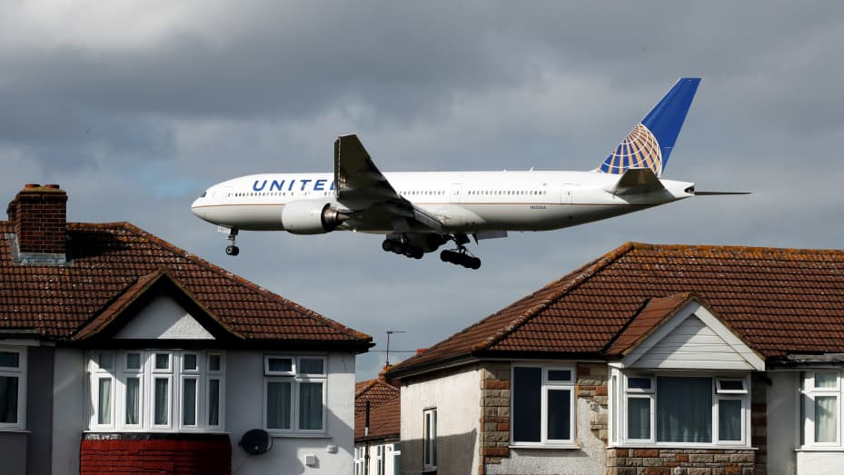 A United Airlines passenger aircraft arrives over the top of residential houses to land at Heathrow Airport in west London, Britain, March 13, 2020.