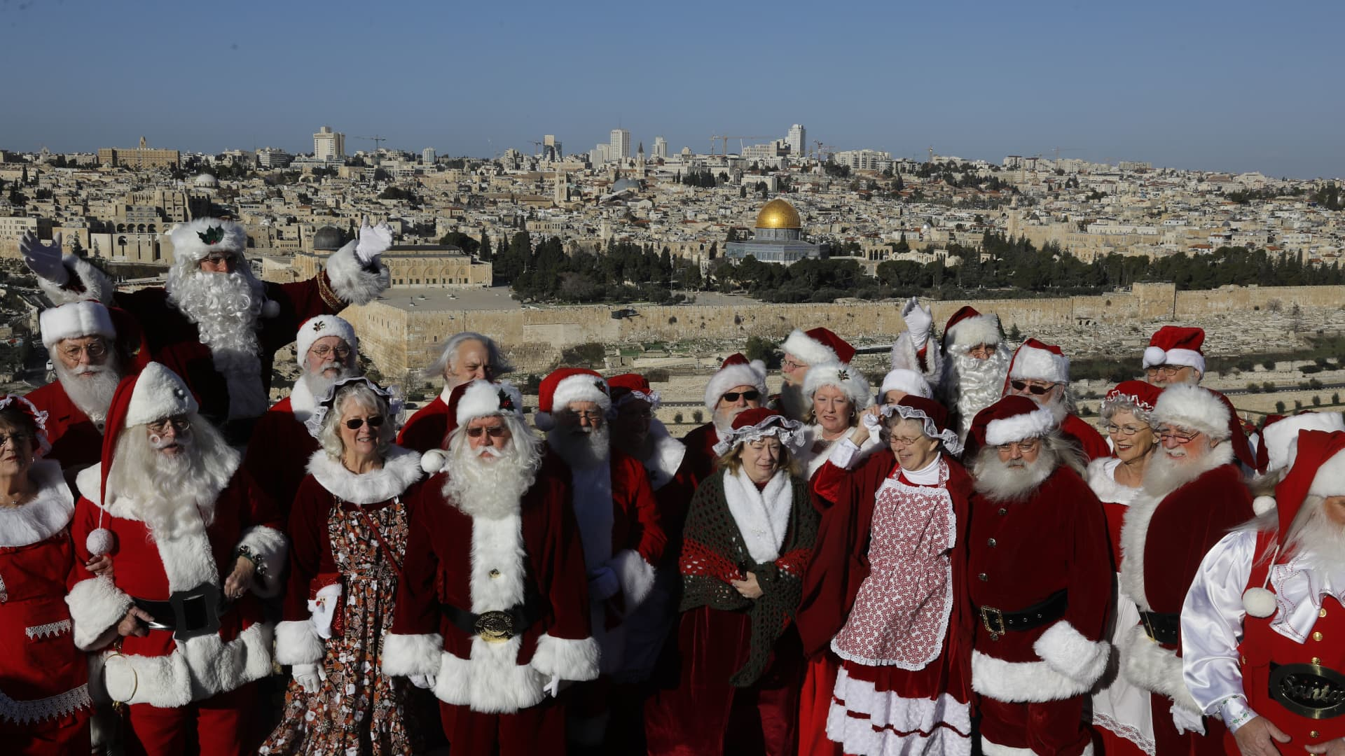 A group people dressed as Santa Claus visit the Mount of Olives overlooking Jerusalem's Old City on Jan. 7, 2020.