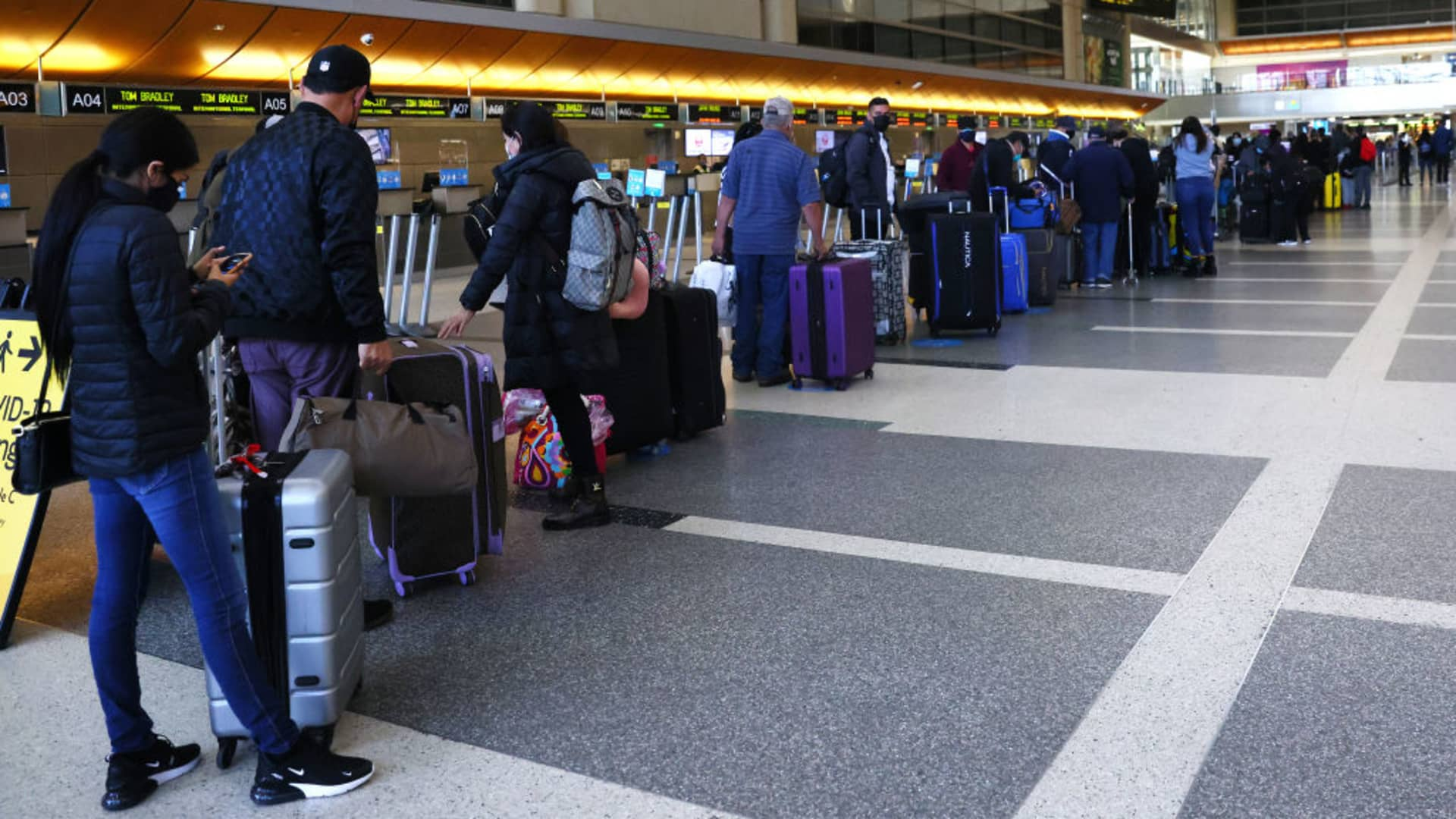 Travelers wait in line to check in at the Tom Bradley International Terminal at Los Angeles International Airport (LAX) amid a COVID-19 surge in Southern California on December 22, 2020 in Los Angeles, California.