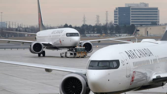 An Air Canada Boeing 737 MAX 8 aircraft is being towed in as another Air Canada Boeing 737 MAX 8 aircraft is seen on the ground at Toronto Pearson International Airport in Toronto, Ontario, Canada, March 13, 2019.