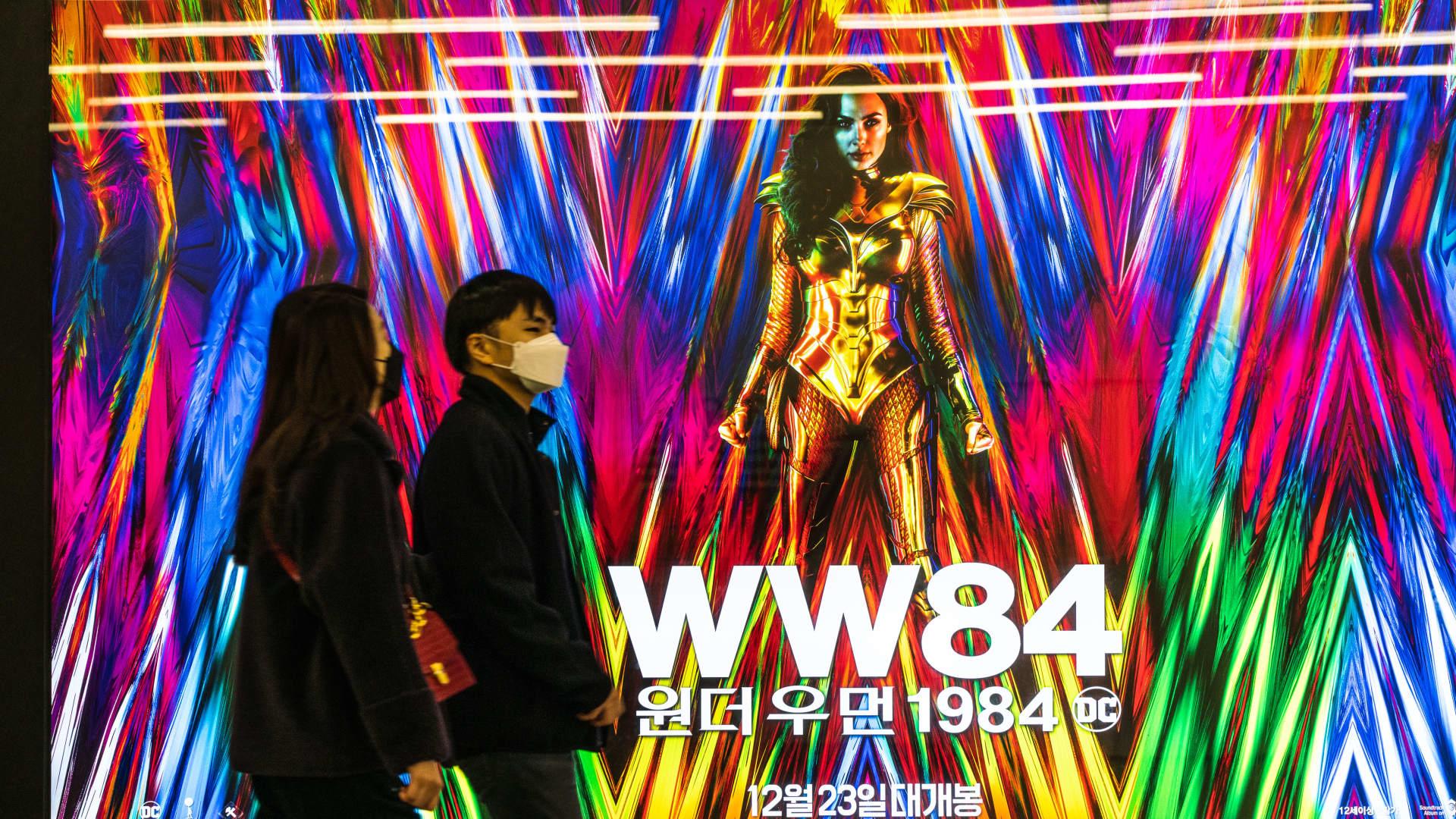 People wearing masks walk past an advertising billboard of the movie 'Wonder Woman 1984'. Photo taken on 26 Dec. 2020.