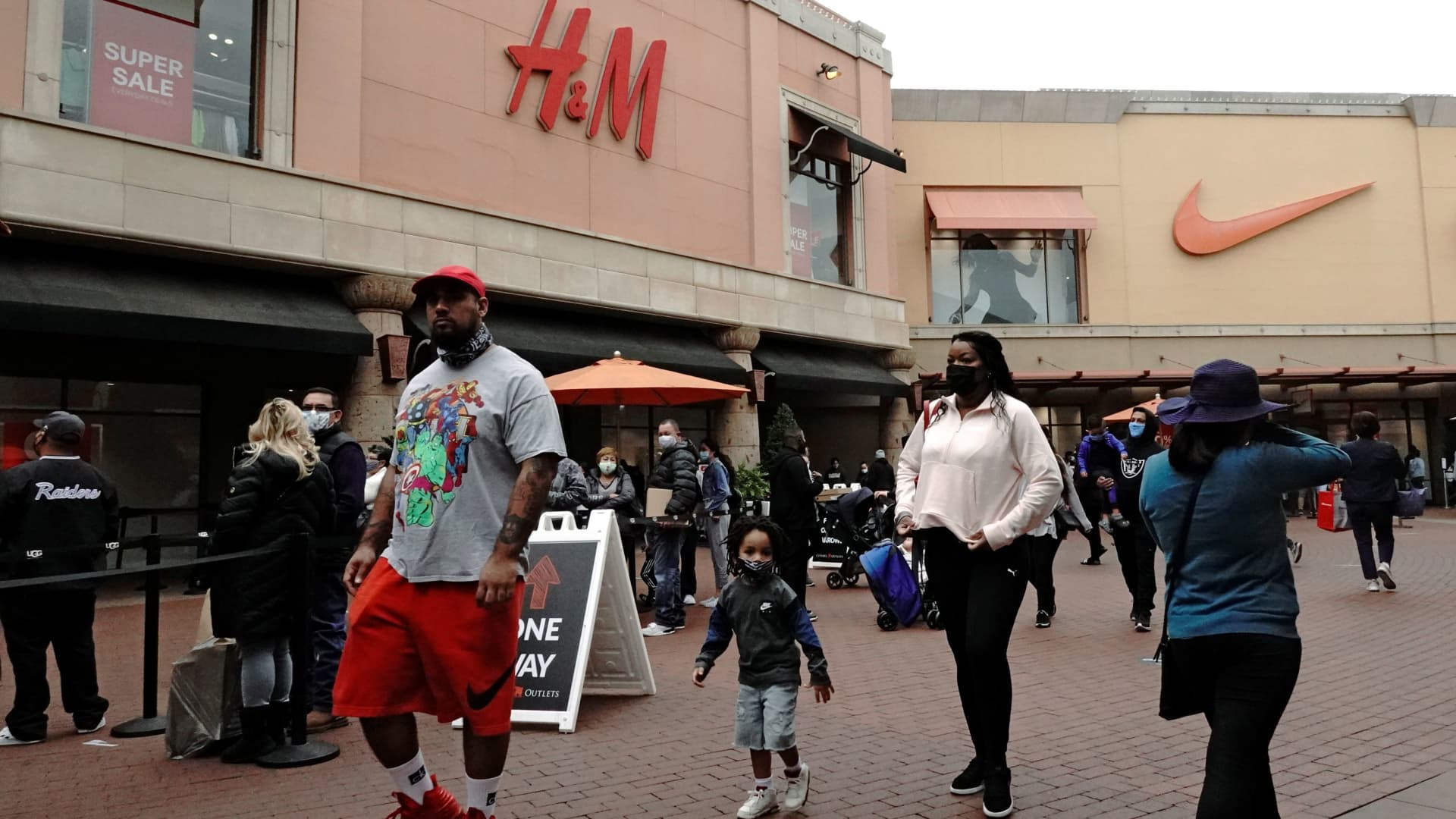 A family walks past people queuing to enter H&M and Nike stores at Citadel Outlets as the coronavirus disease (COVID-19) cases surge in Commerce, California, December 27, 2020.