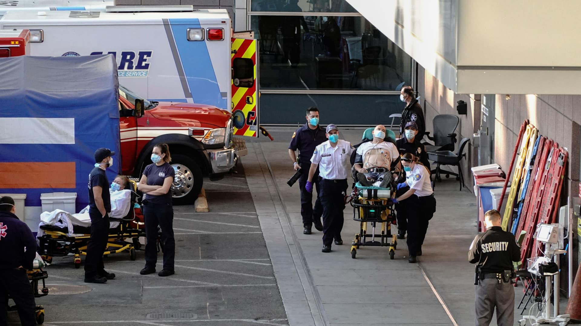 Paramedics escort a patient from the ambulance entrance to the emergency room at LAC + USC Medical Center during a surge of coronavirus disease (COVID-19) cases in Los Angeles, California, December 27, 2020.