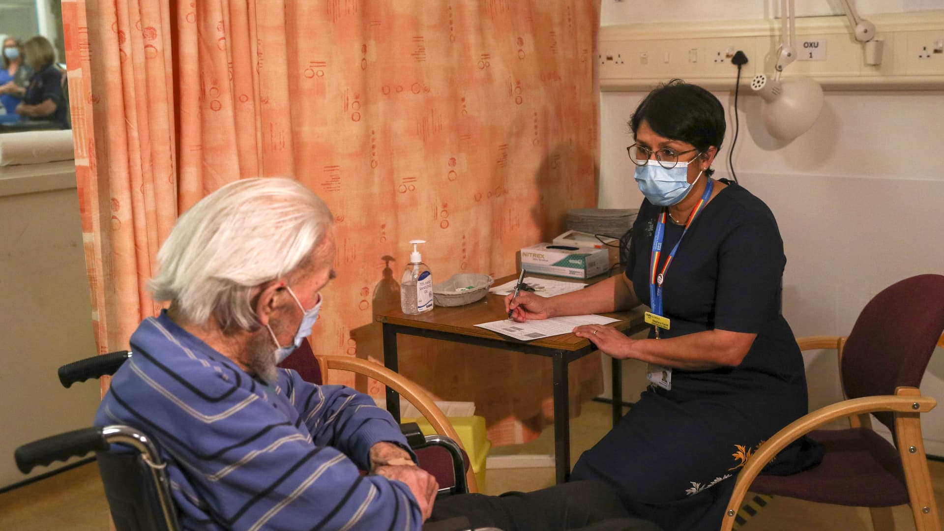 Meghana Pandit, chief medical officer at the Oxford University NHS Trust, right, speaks to Trevor Cowlett, 88, ahead of him receiving the AstraZeneca Plc and the University of Oxford Covid-19 vaccine at the Churchill Hospital in Oxford, U.K., on Monday, Jan. 4, 2021. U.K. regulators cleared the shot last week, marking its first approval worldwide.