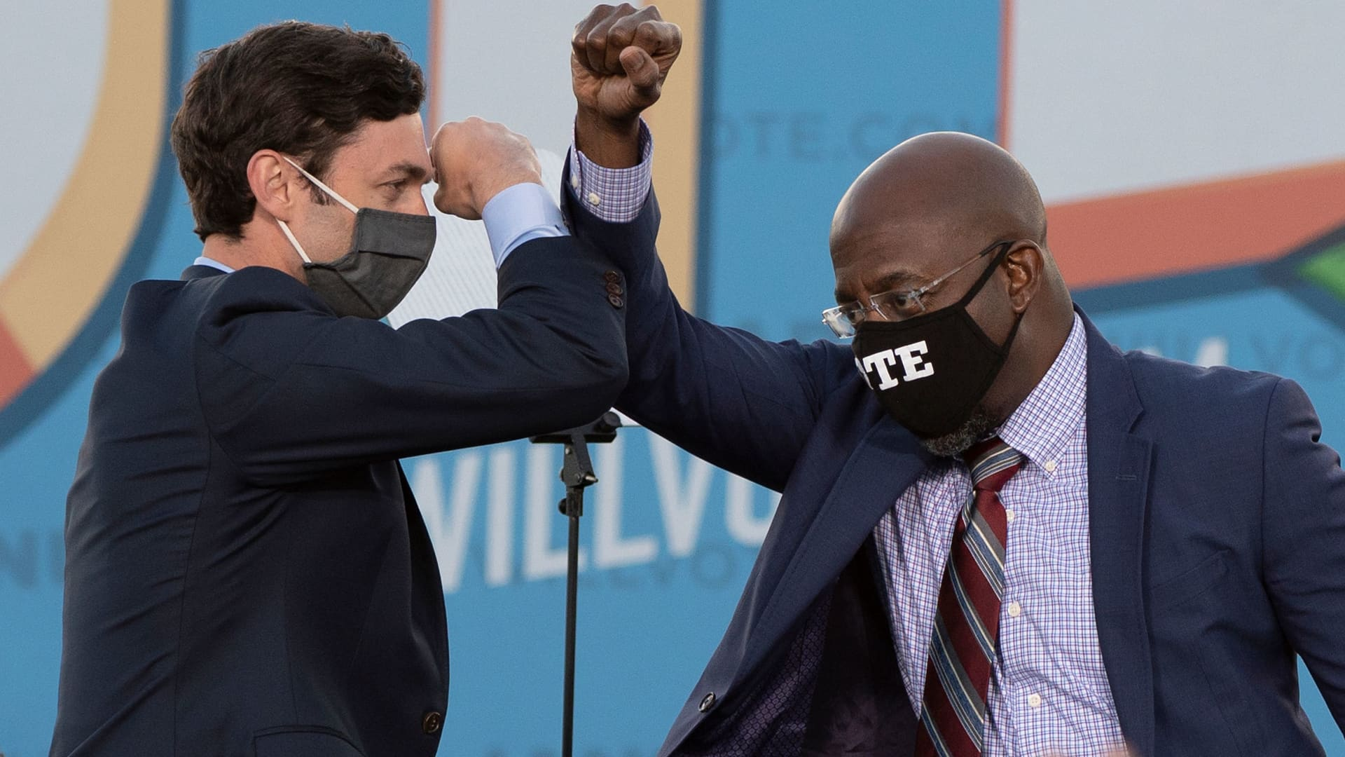 Democratic candidates for Senate Jon Ossoff (L) and Raphael Warnock (R) bump elbows on stage during a rally with US President-elect Joe Biden outside Center Parc Stadium in Atlanta, Georgia, on January 4, 2021.
