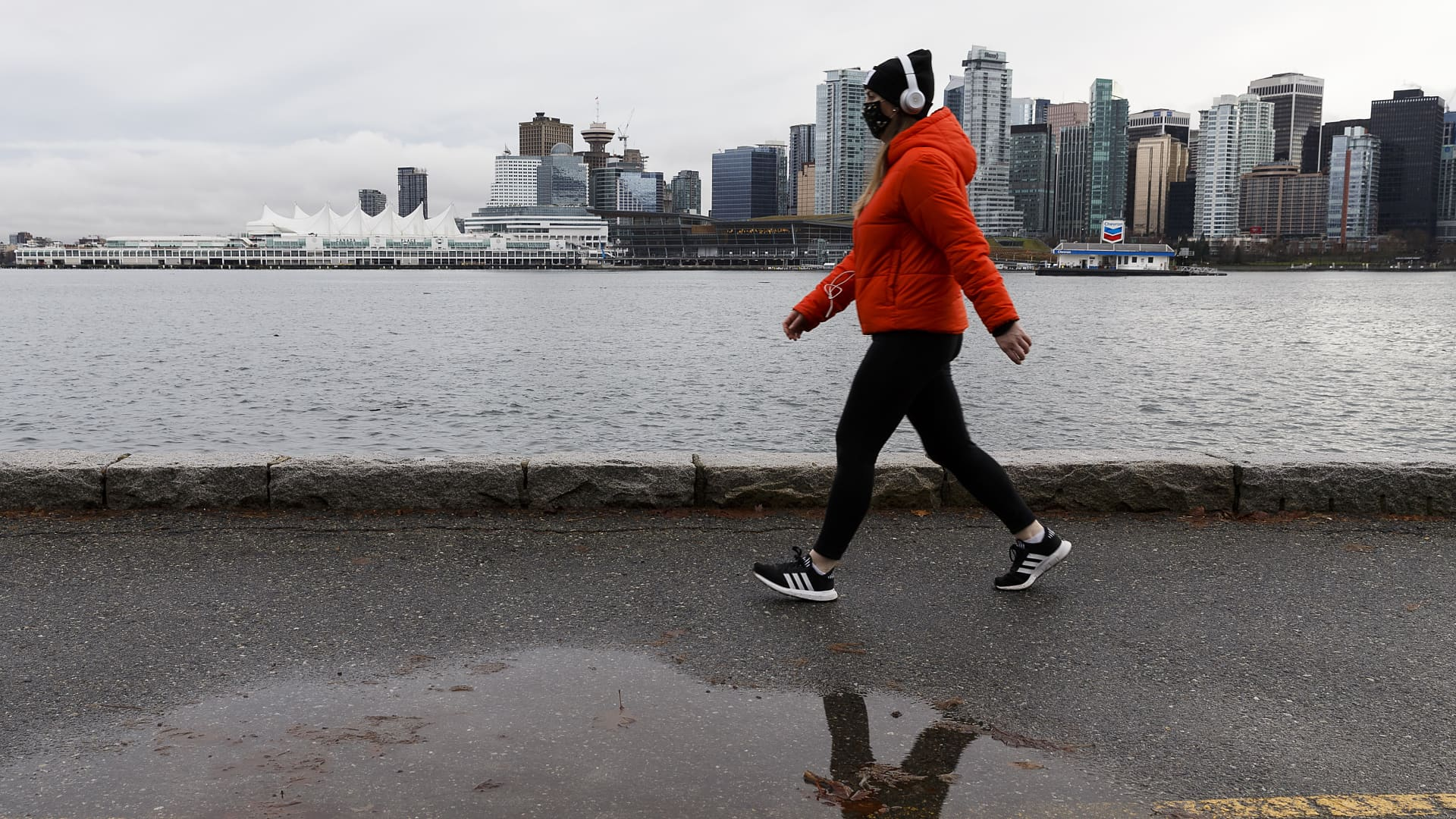 A woman wearing a protective face mask walks on the seawall at Stanley Park on January 04, 2021 in Vancouver, Canada.