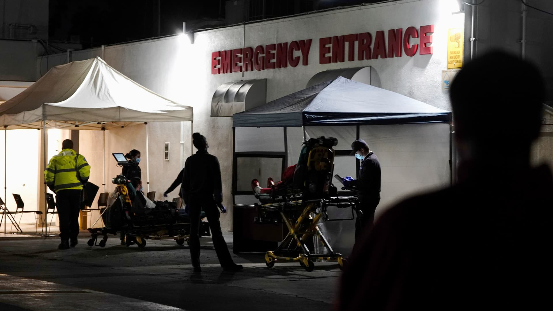 Emergency medical technicians (EMTs) and healthcare workers treat patients outside the emergency room at the Community Hospital of Huntington Park during a surge in positive coronavirus disease (COVID-19) cases in Huntington Park, California, December 29, 2020.