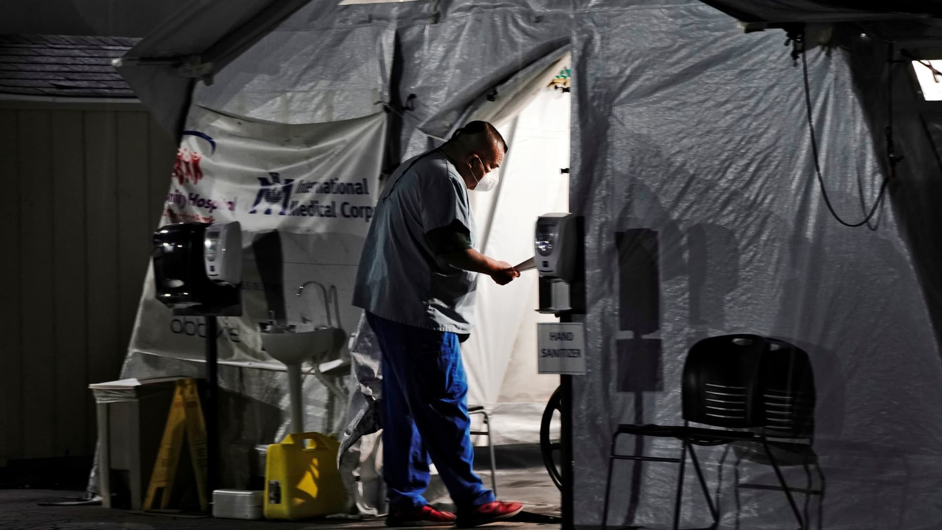 A healthcare worker checks on patients inside an oxygen tent outside the emergency room at the Community Hospital of Huntington Park during a surge in positive coronavirus (COVID-19) cases in Huntington Park, California, December 29, 2020.