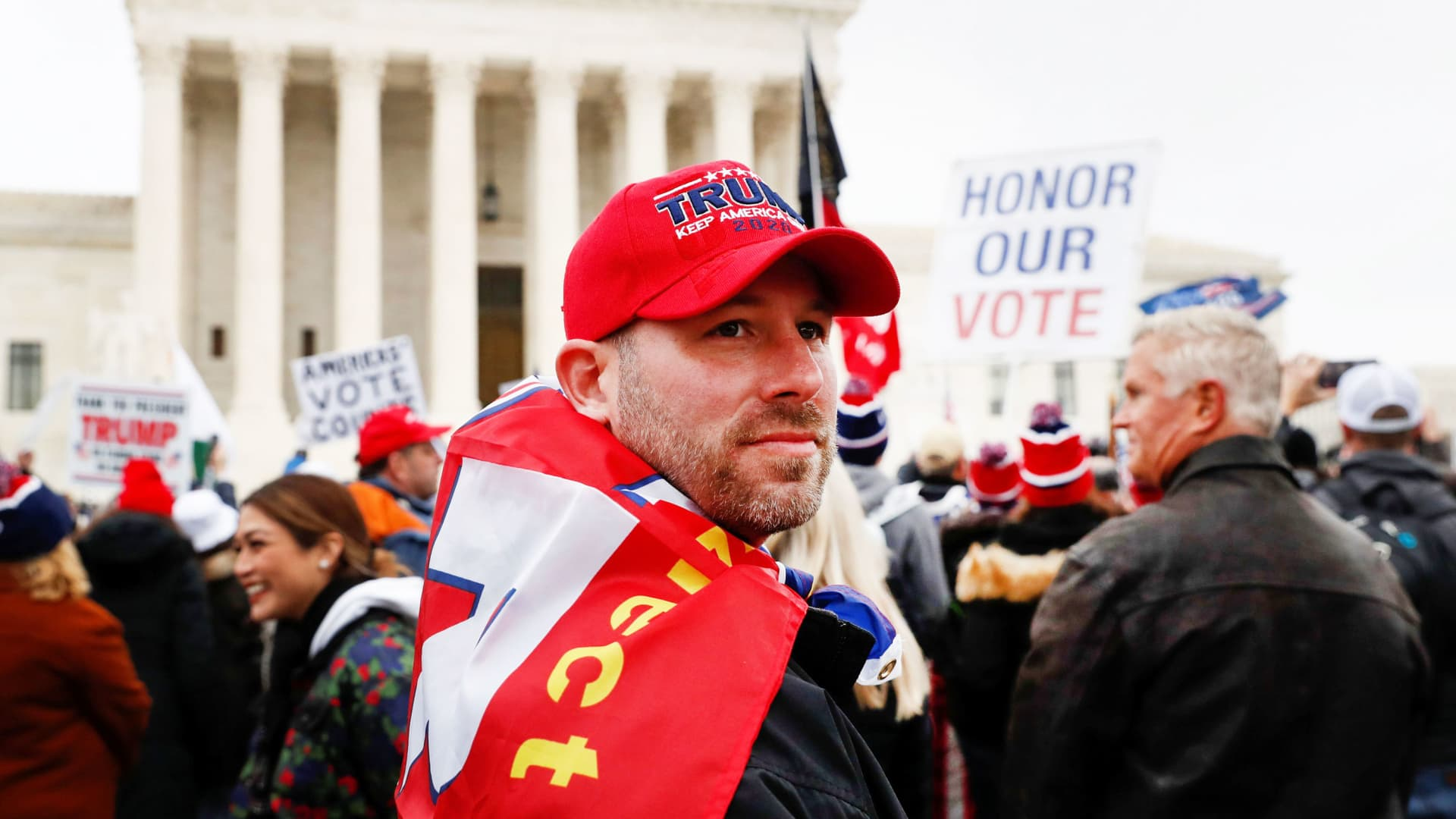 A supporter of U.S. President Donald Trump looks on as others gather in front of the Supreme Court building ahead of the U.S. Congress certification of the November 2020 election results during protests in Washington, January 5, 2021.